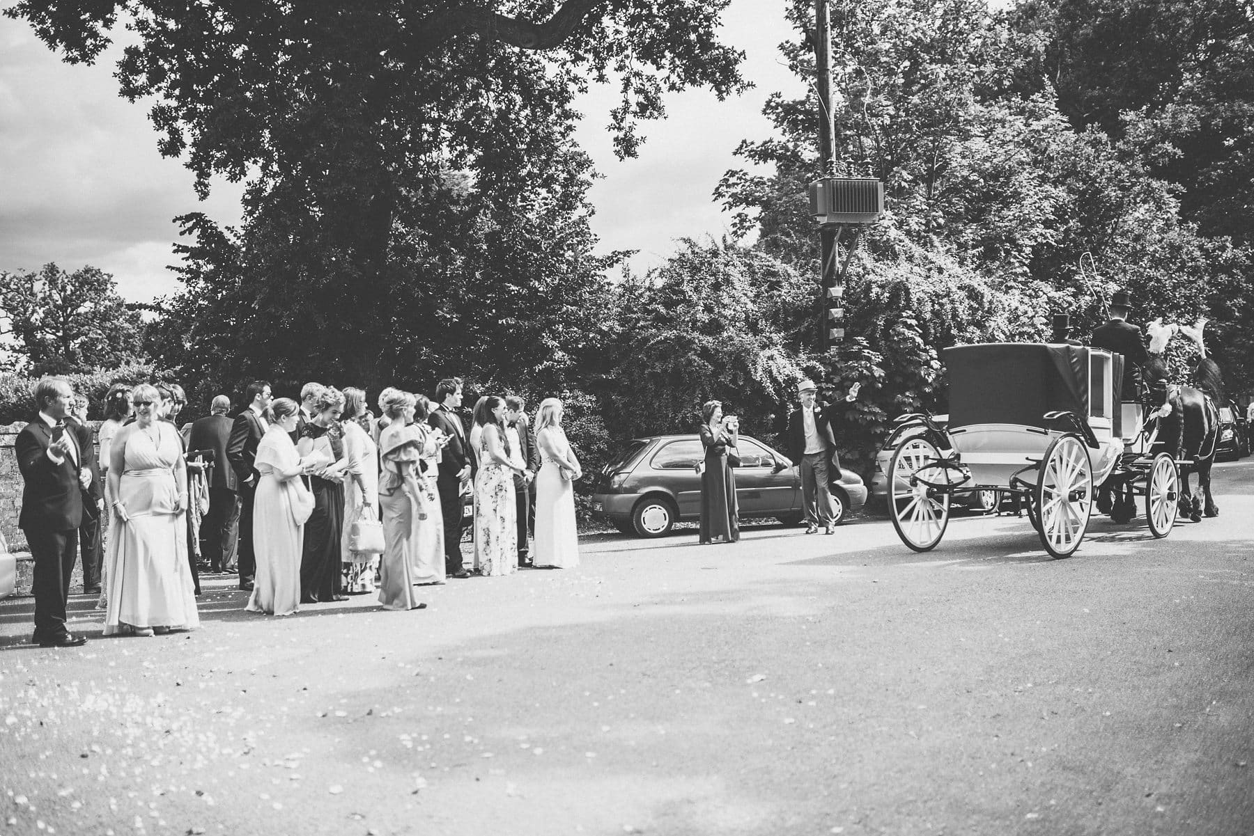 Wedding guests waving off the bride and groom in their horse drawn carriage bound for their Coworth Park barn summer wedding photography