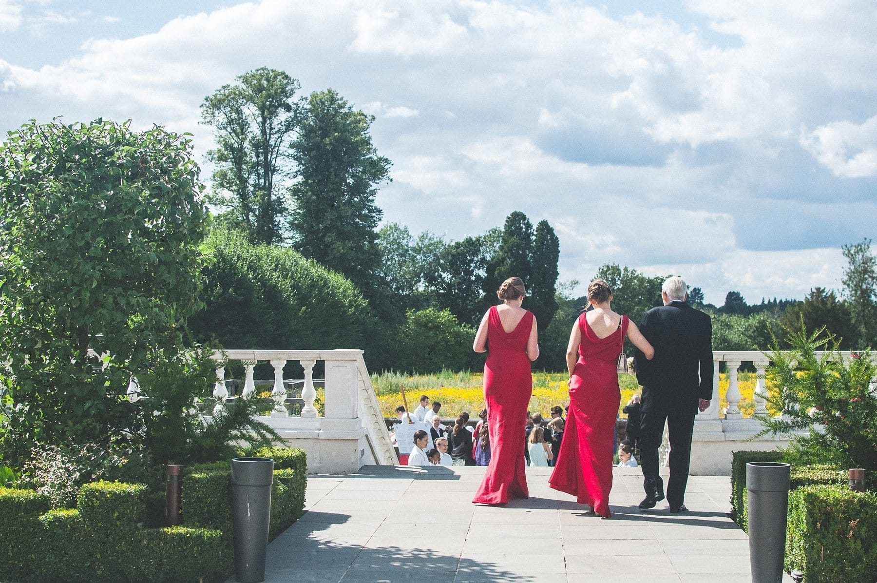 Bridesmaids and grandfather of the bride walking down Coworth Park mansion steps