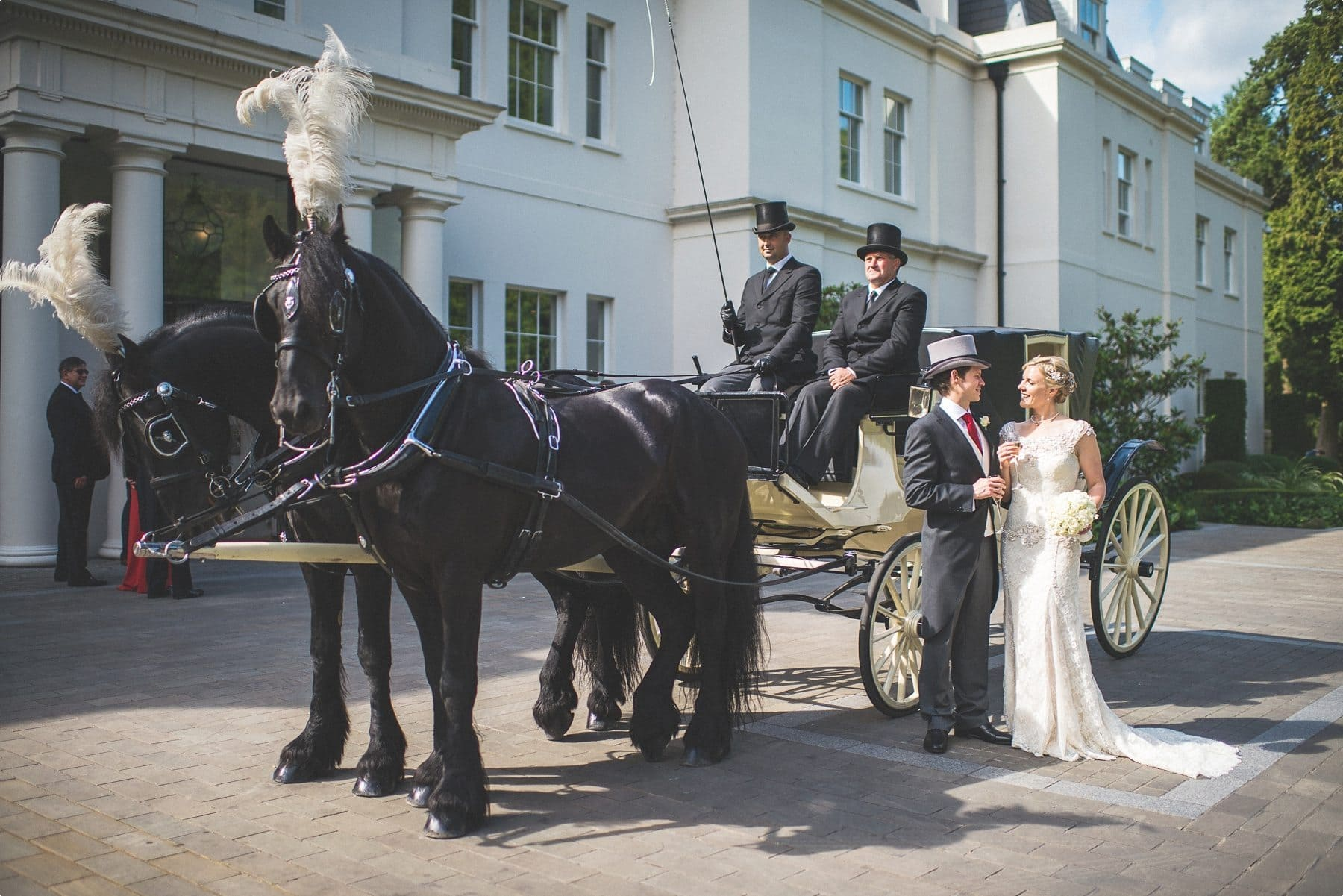 Bride and groom smiling at each other standing by their horse drawn carriage at their Coworth Park Barn summer wedding