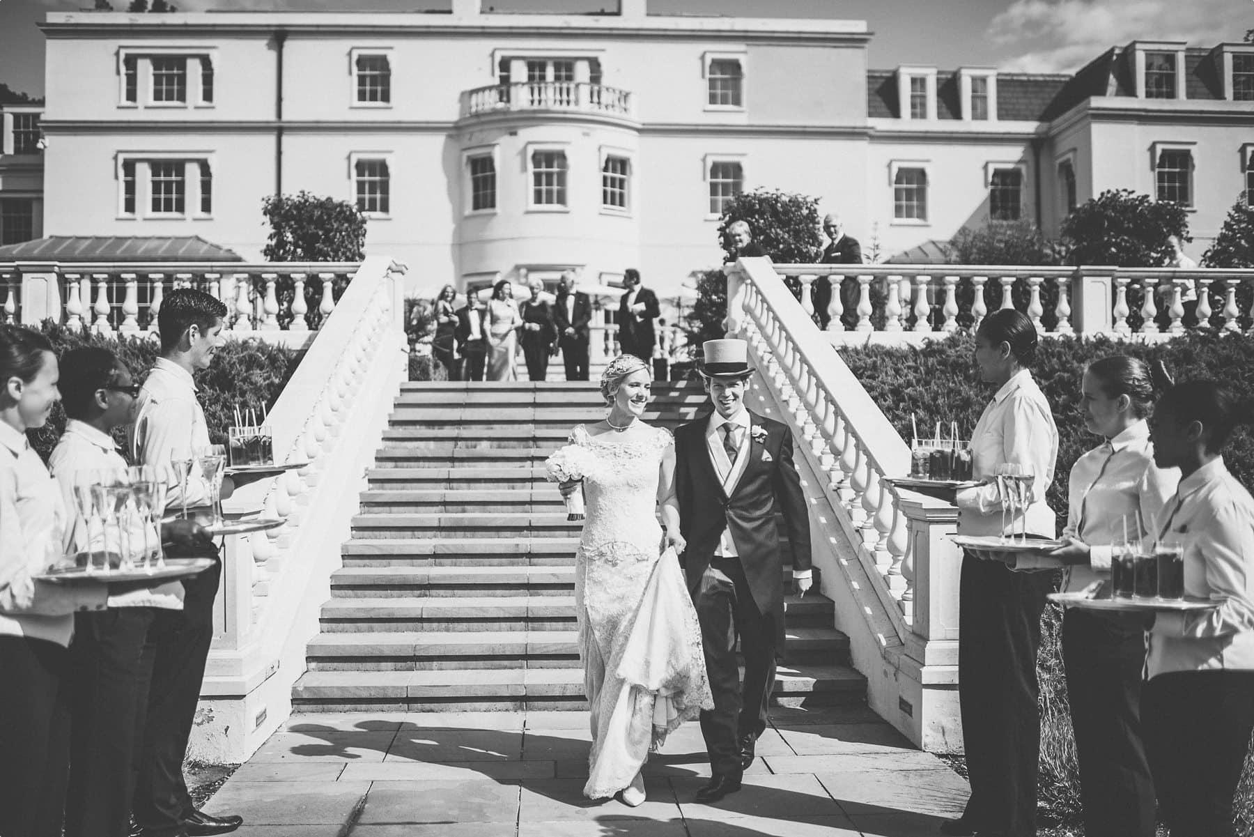 Bride and groom walking down Coworth Park mansion steps
