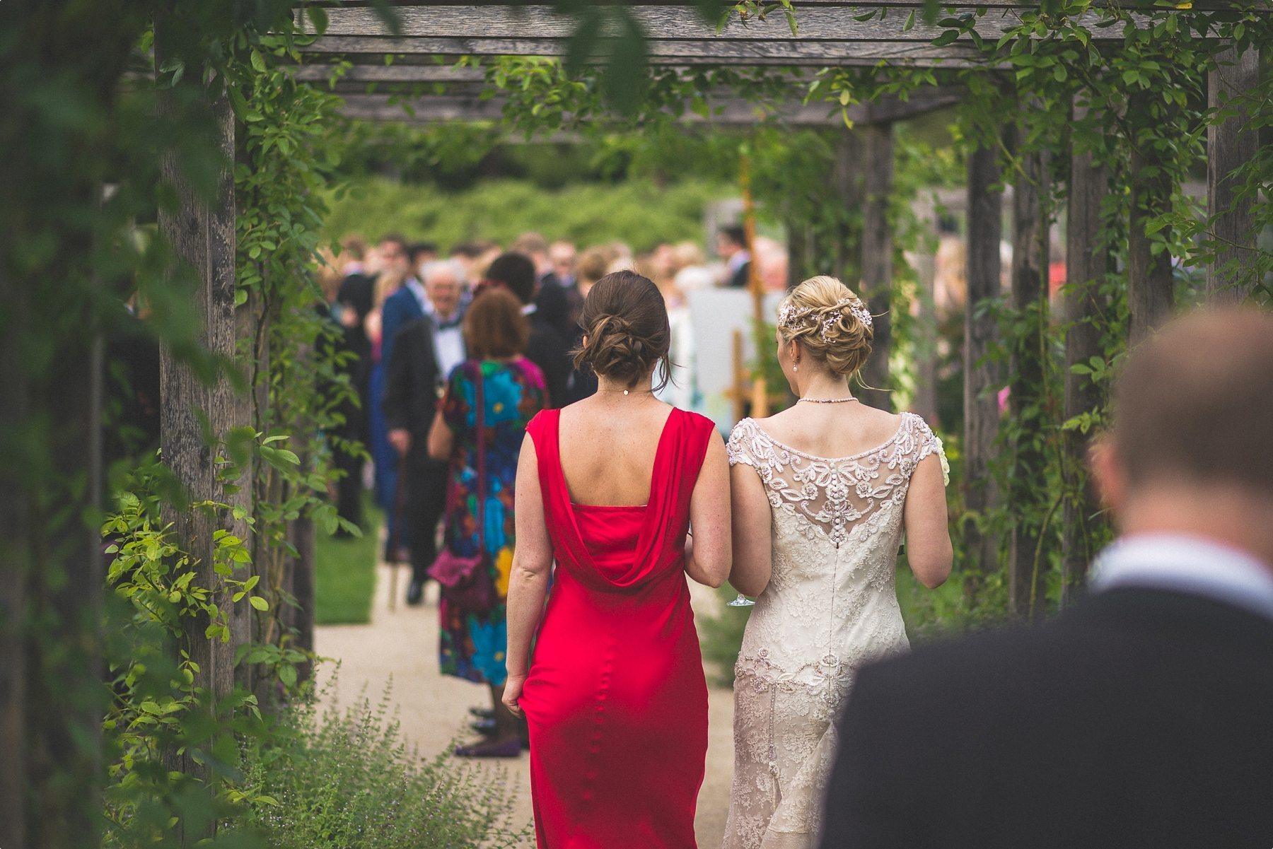 Bride and bridesmaid walking through the grounds at her Coworth Park Barn Summer wedding to join the other guests