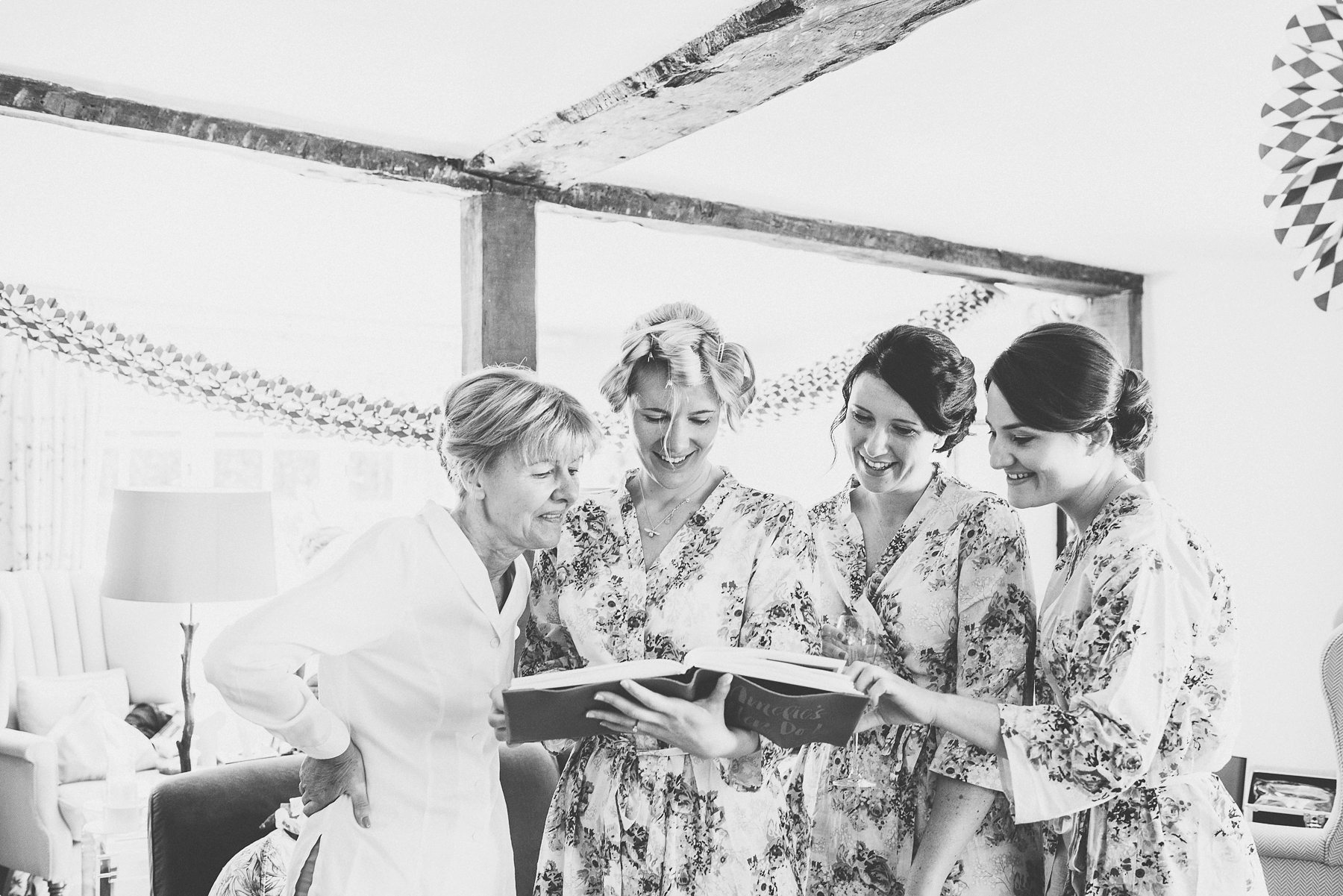 Bride and bridesmaids looking at gift hen do book