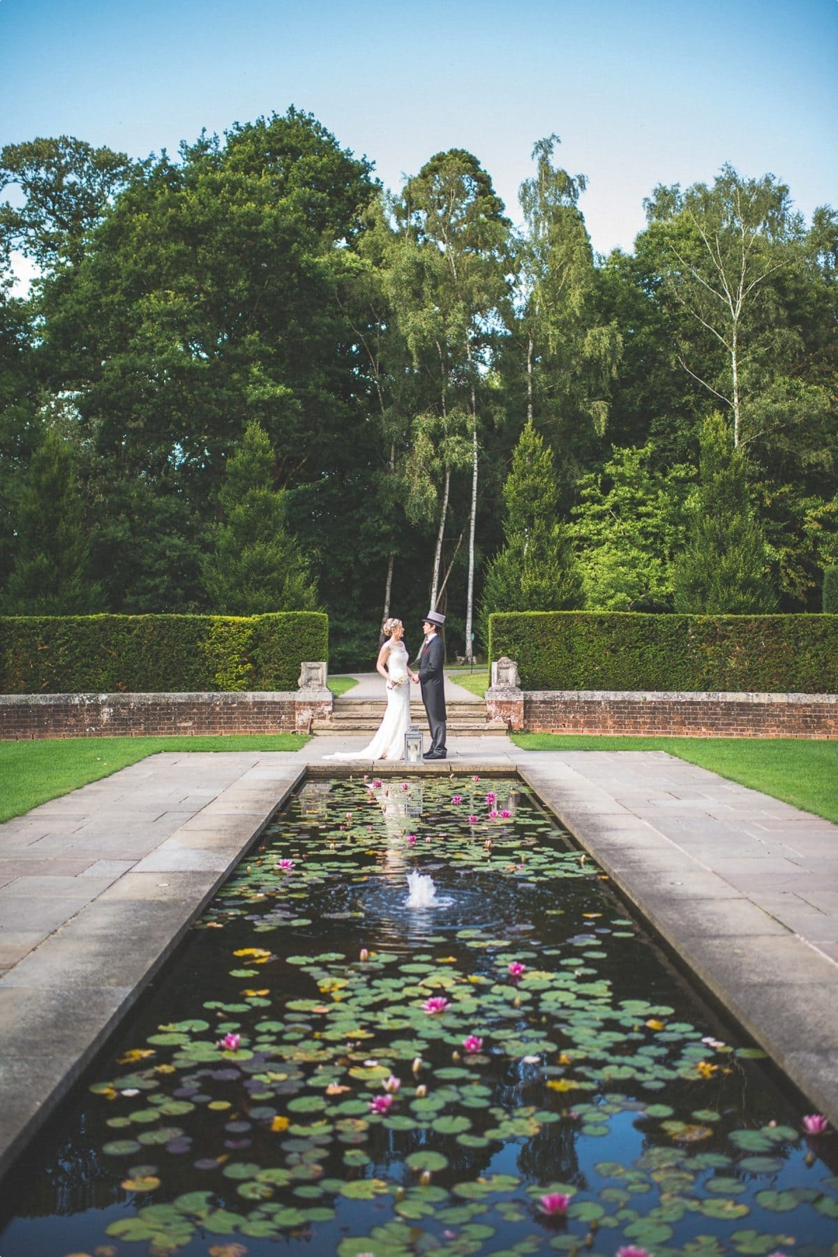 Bride and groom summer wedding portrait at coworth park lily pond awesome couple shoot location