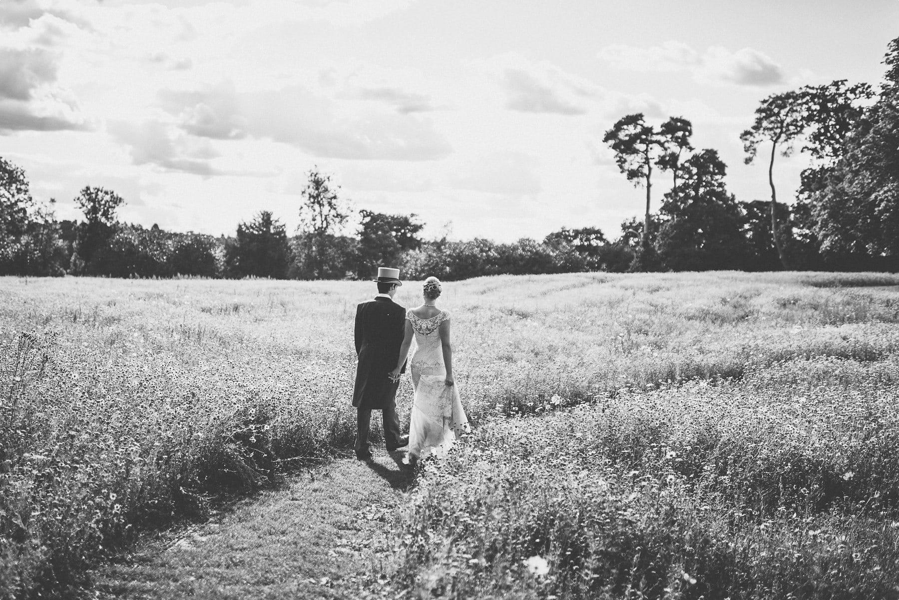 Bride and Groom walking into Coworth Park barn summer wedding wildflower meadow