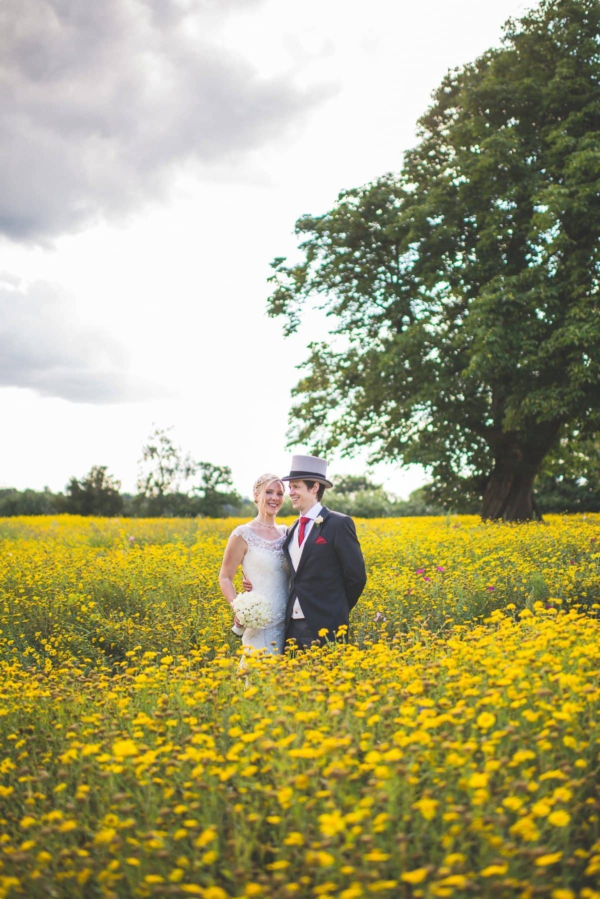 Coworth Park wedding photography of a Bride and Groom standing in the wildflower meadow