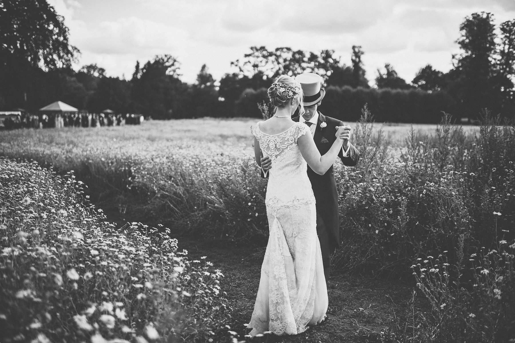 bride and groom practicing their first dance at Coworth Park wild flower meadow