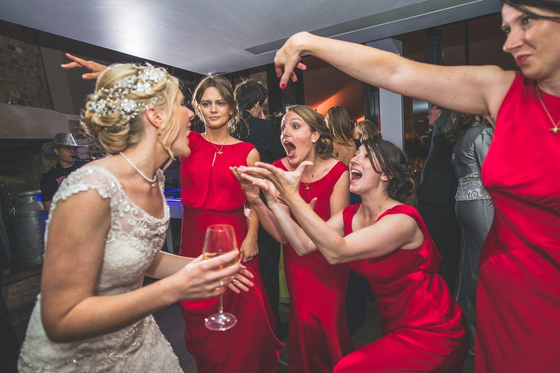 bride and bridesmaids singing and dancing at Coworth Park barn summer wedding