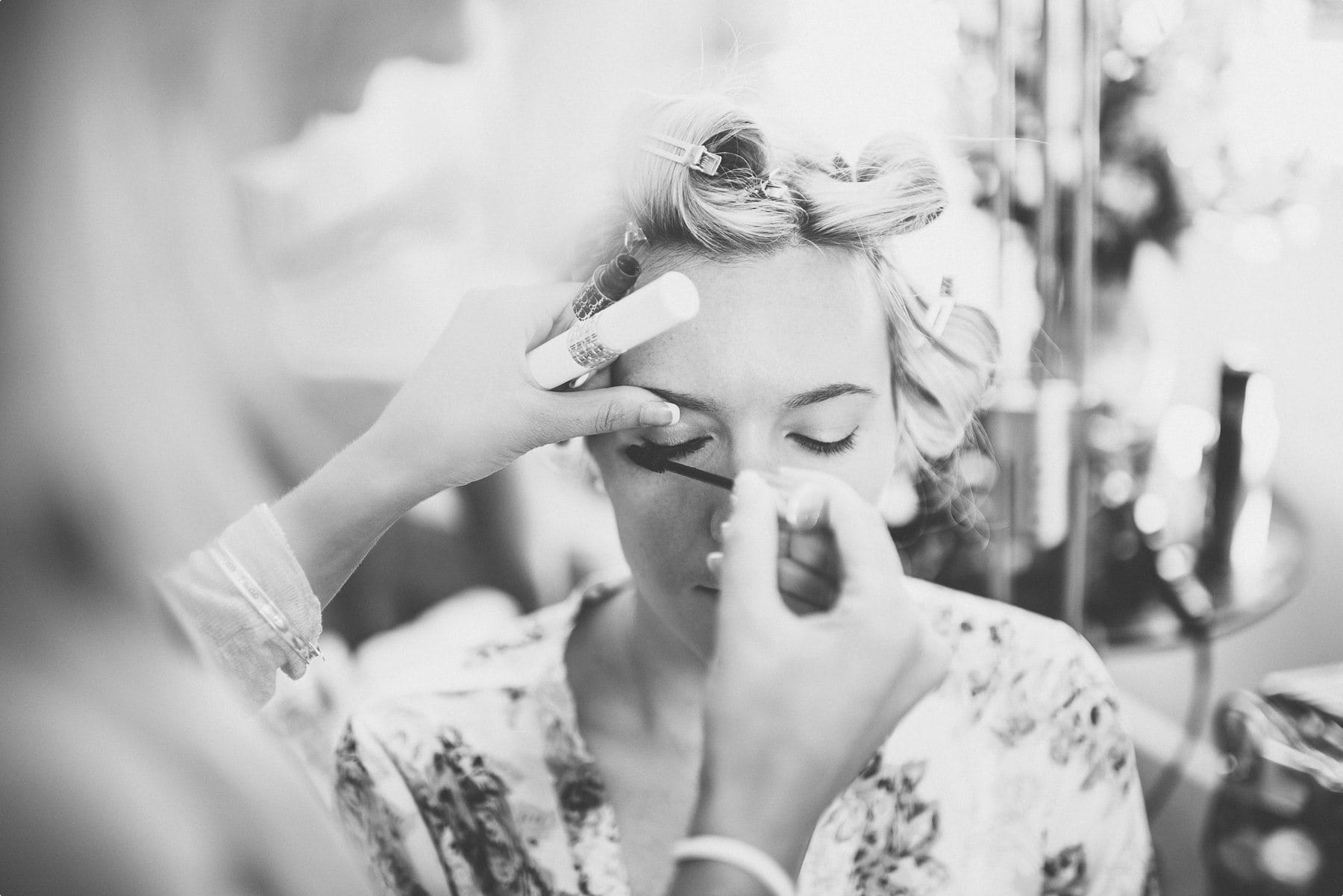 Bride's makeup being applied at Coworth Park barn wedding dower house