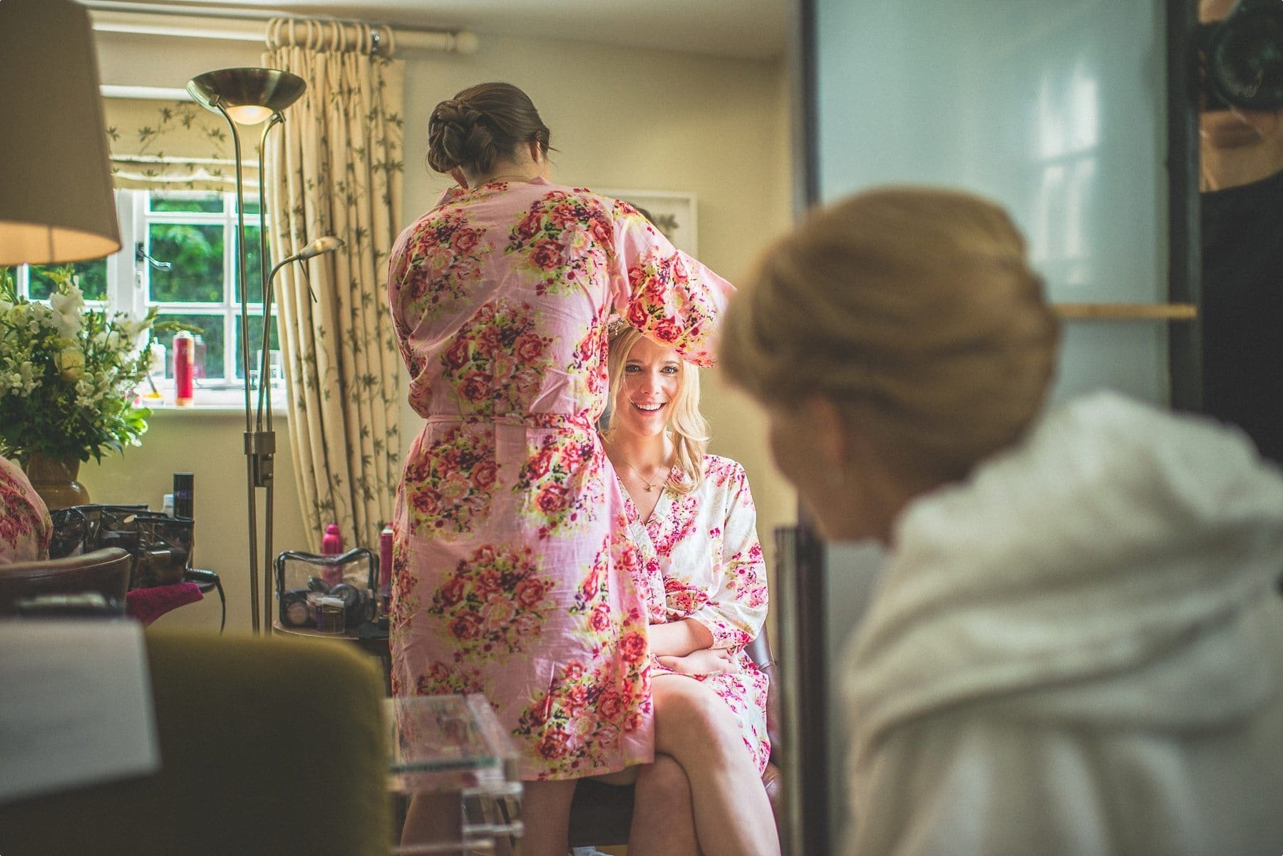 bride and mum exchanging a glance as they prepare for her Coworth Park barn summer wedding