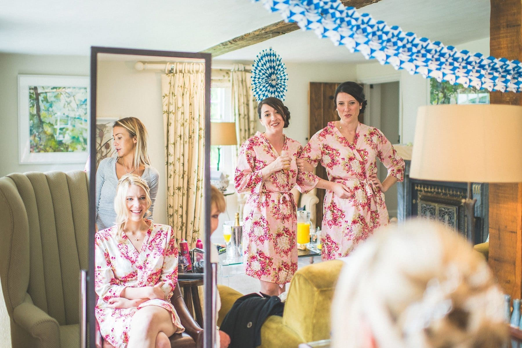 bridesmaids looking at the bride and the bride's reflection looking at them at the dower house at coworth park barn