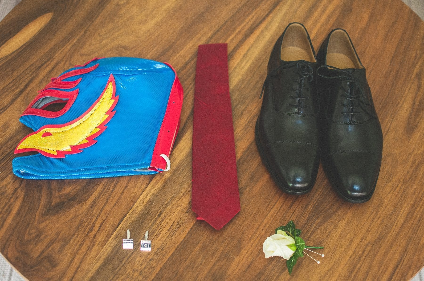 Groom's outfit and Mexican Wrestling mask laid out at coworth park barn stables