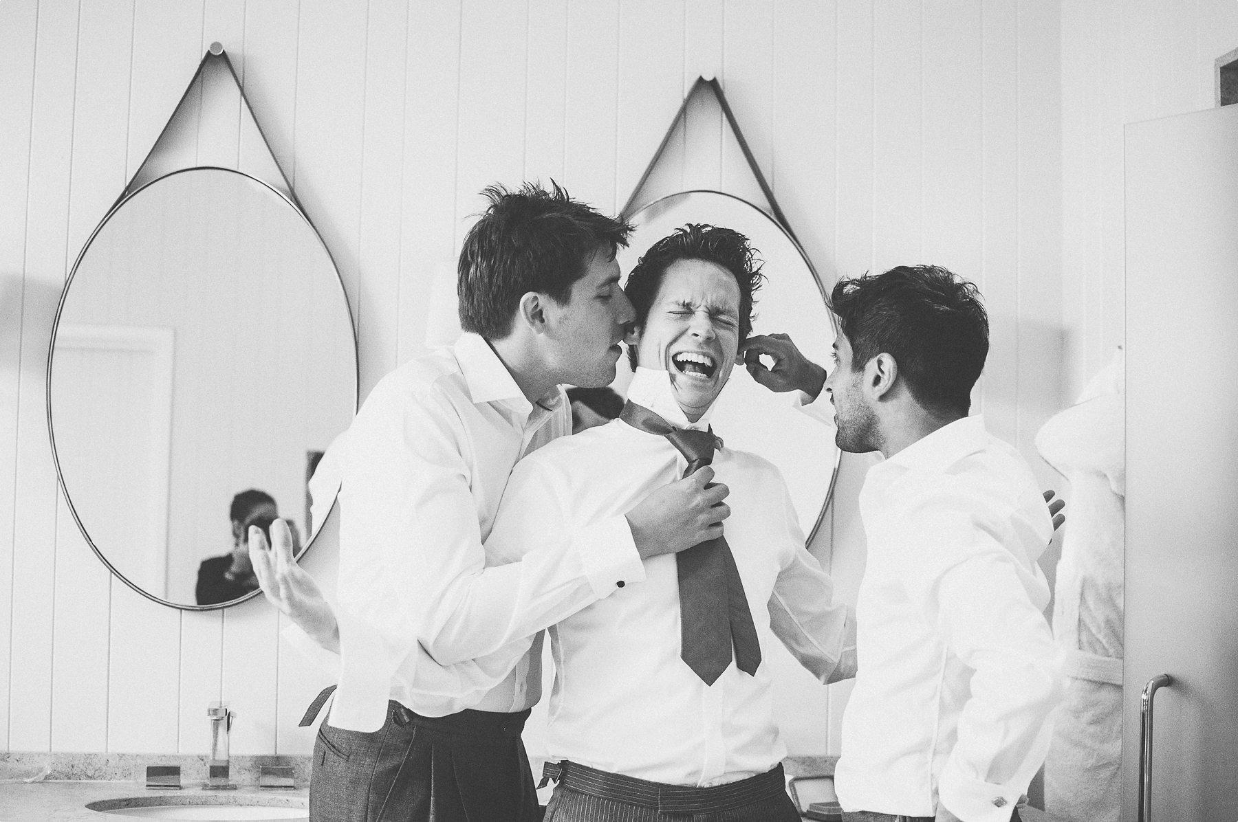 Groomsmen tickling the groom at coworth park barn stables