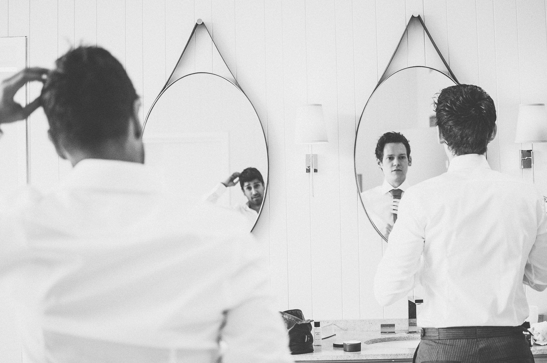 groom and groomsman readying themselves at coworth park barn stables