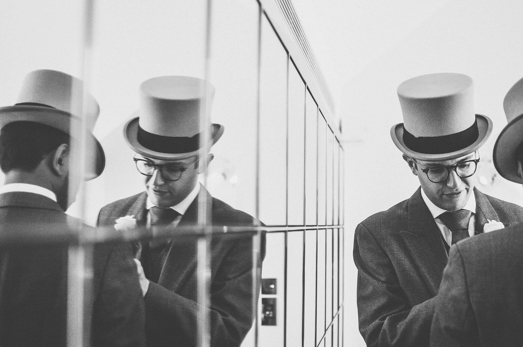 Groomsmen getting ready and their reflection in the mirror at Coworth Park barn stables
