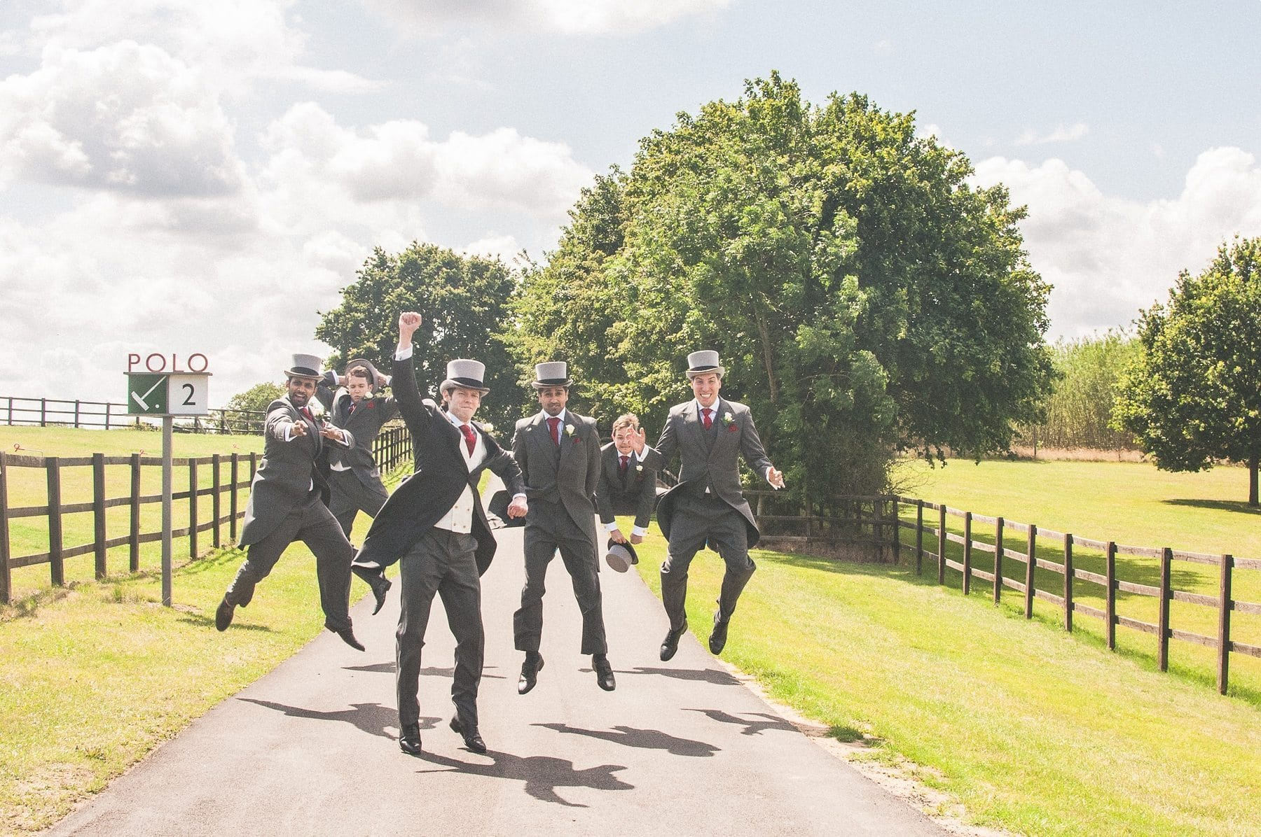 Groom and groomsmen jumping at Coworth Park summer wedding grounds