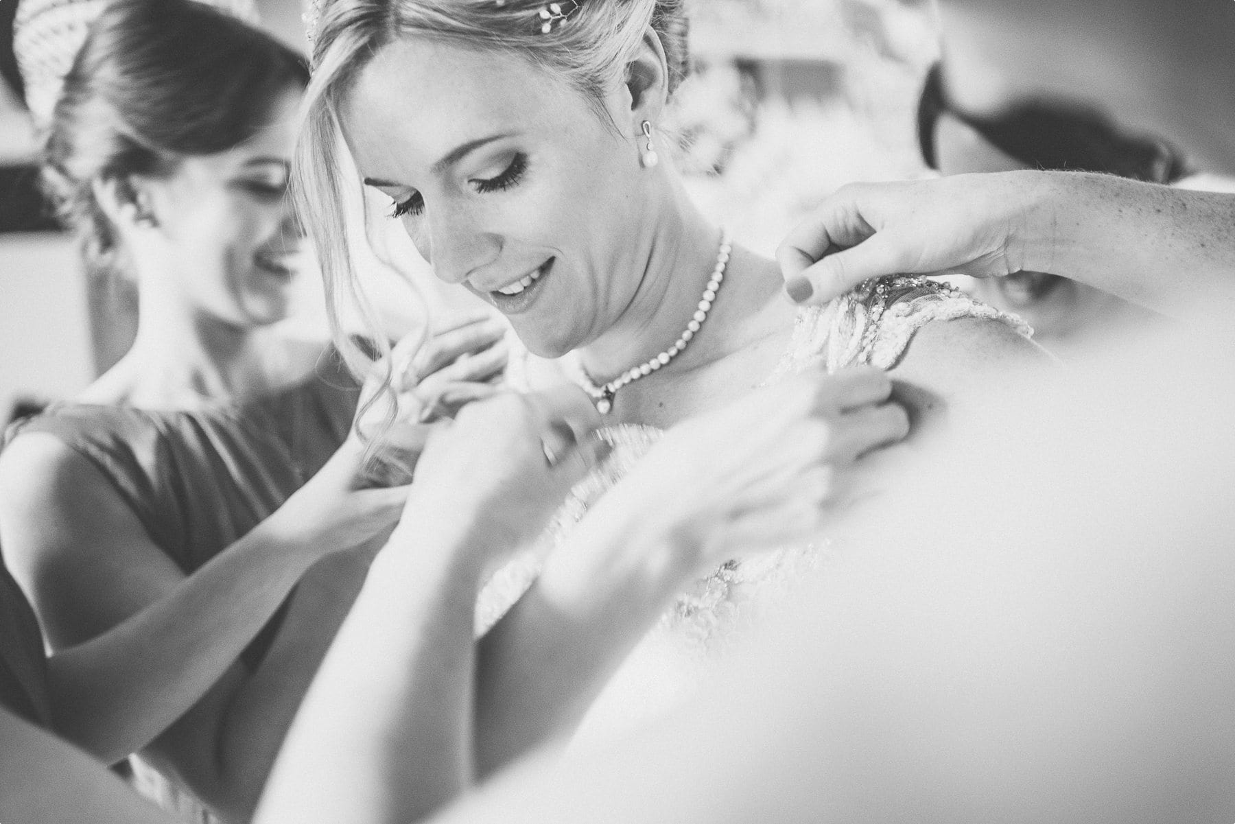 Bridesmaids helping the bride put on her pronovias wedding dress at Coworth Park Dower house