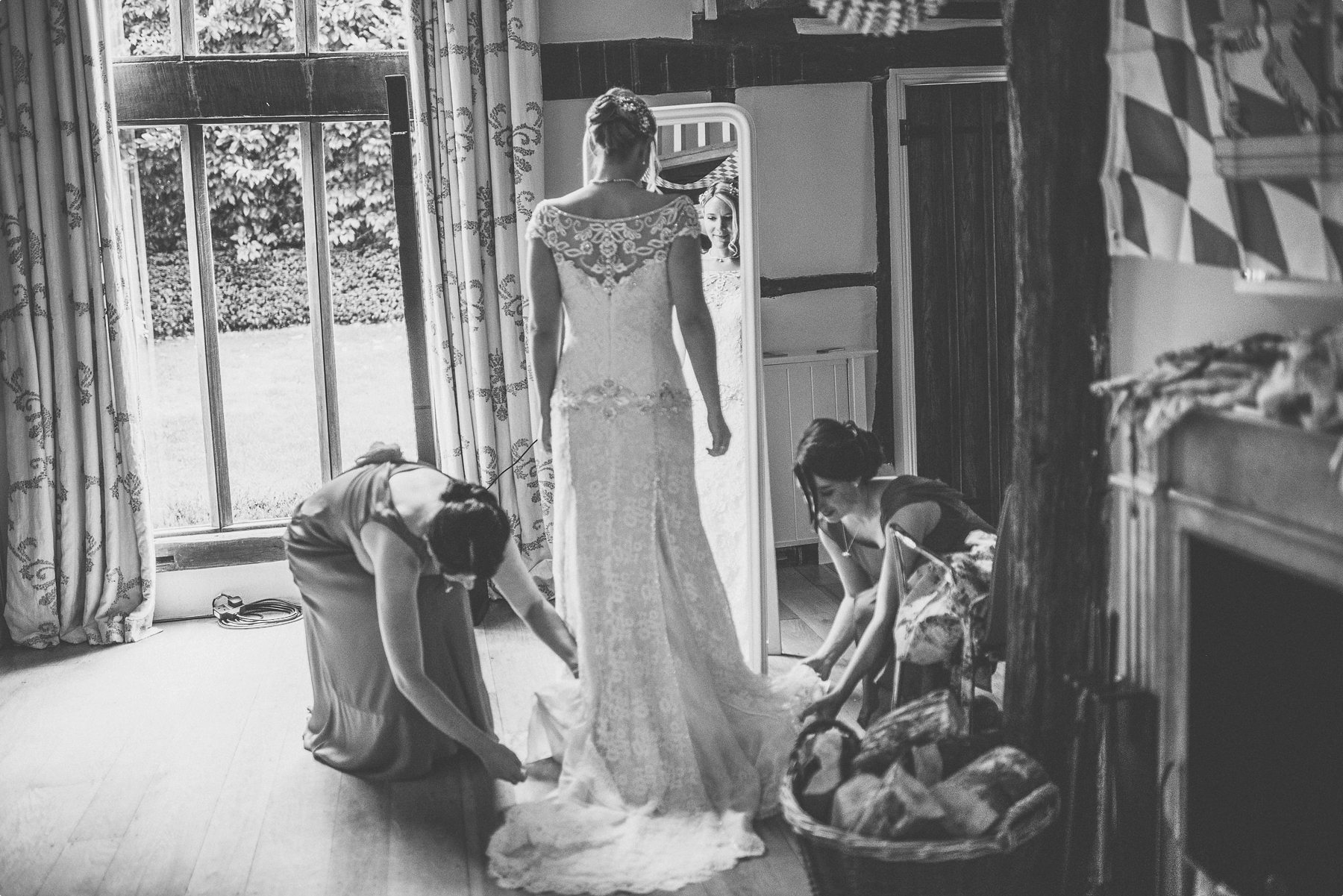 Bridesmaids straightening out the bride's dress at Coworth Park barn's Dower House