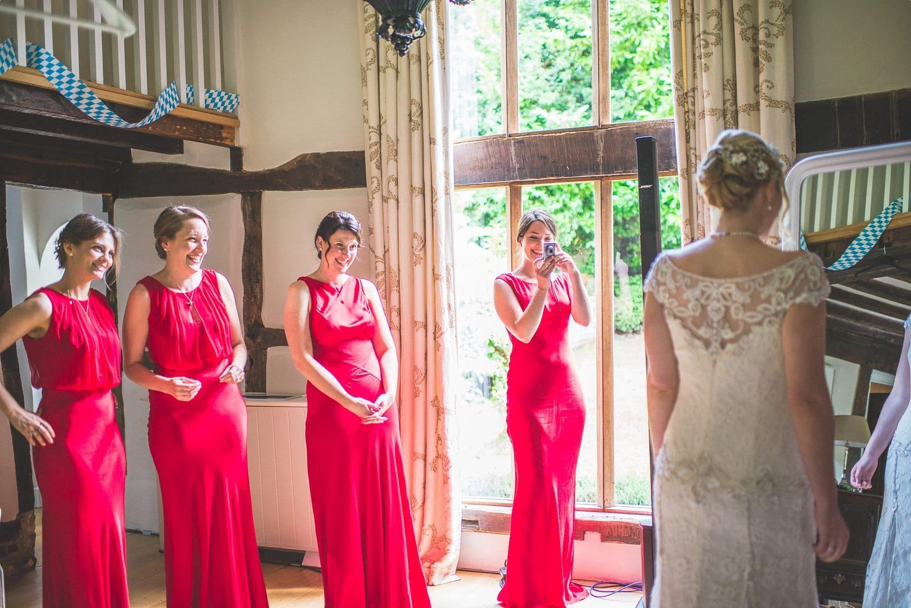 Bridesmaids looking and smiling at the beautiful bride at Coworth Park barn Dower House