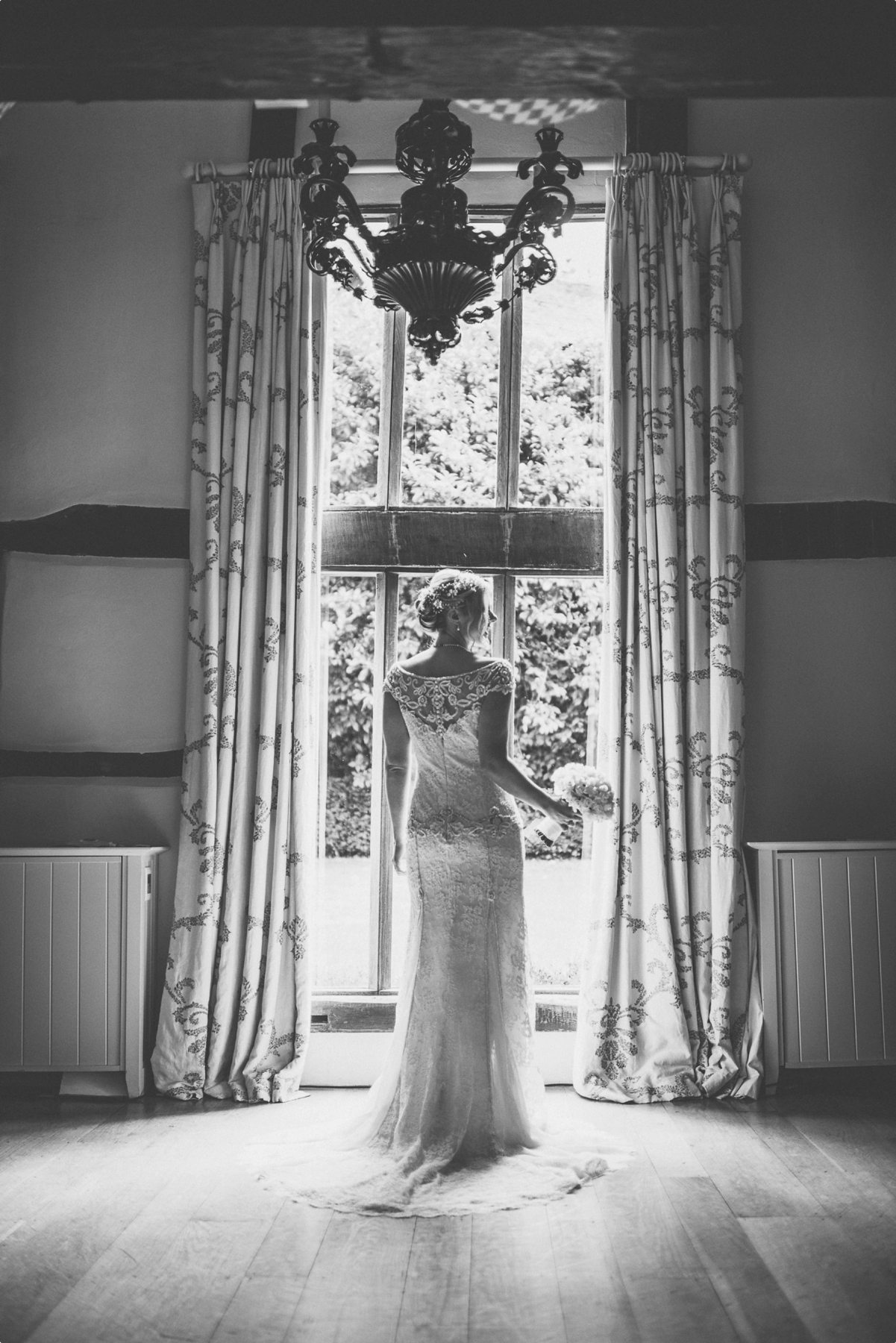 Bride standing in the Dower House window ready for her Coworth Park barn summer wedding
