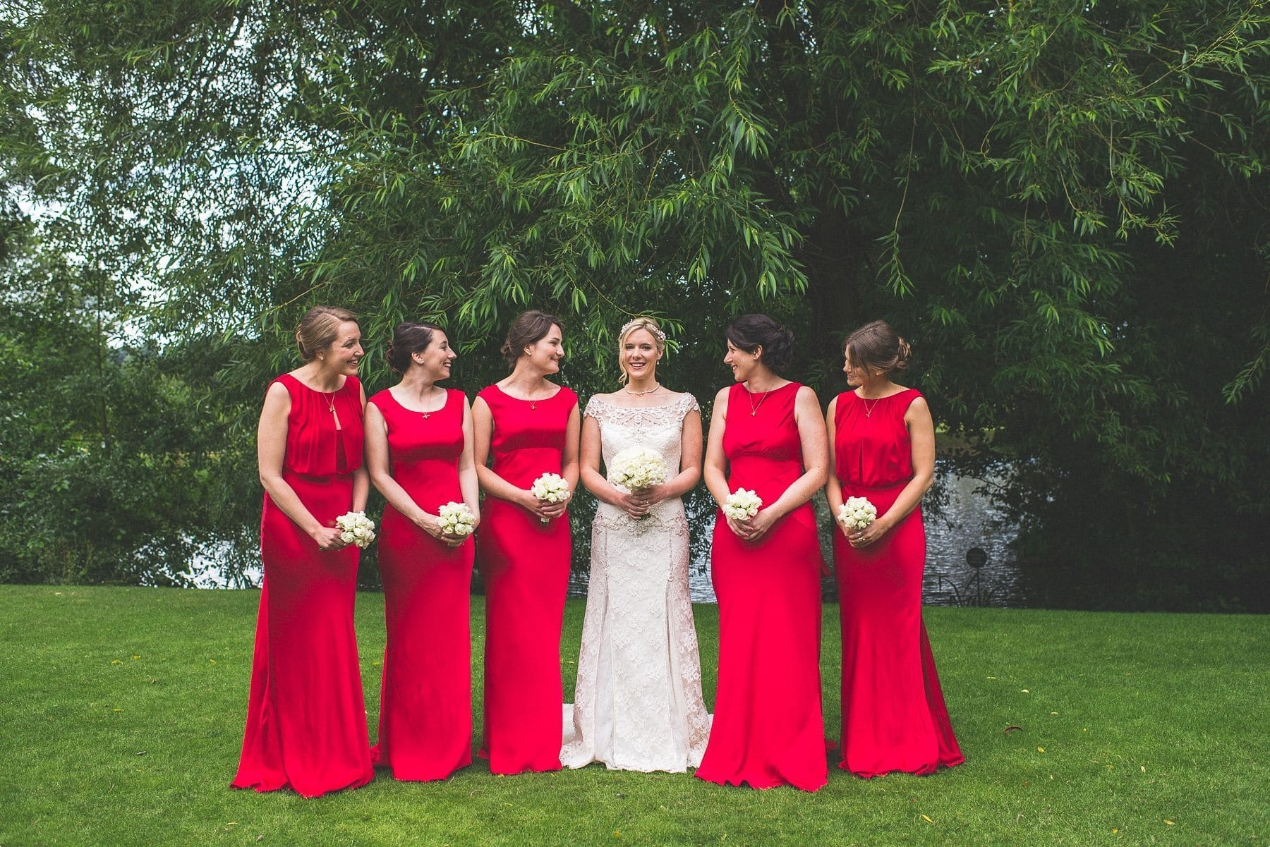 Coworth Park Barn summer wedding photography of the Bride and her bridesmaids wearing red bridesmaids dresses