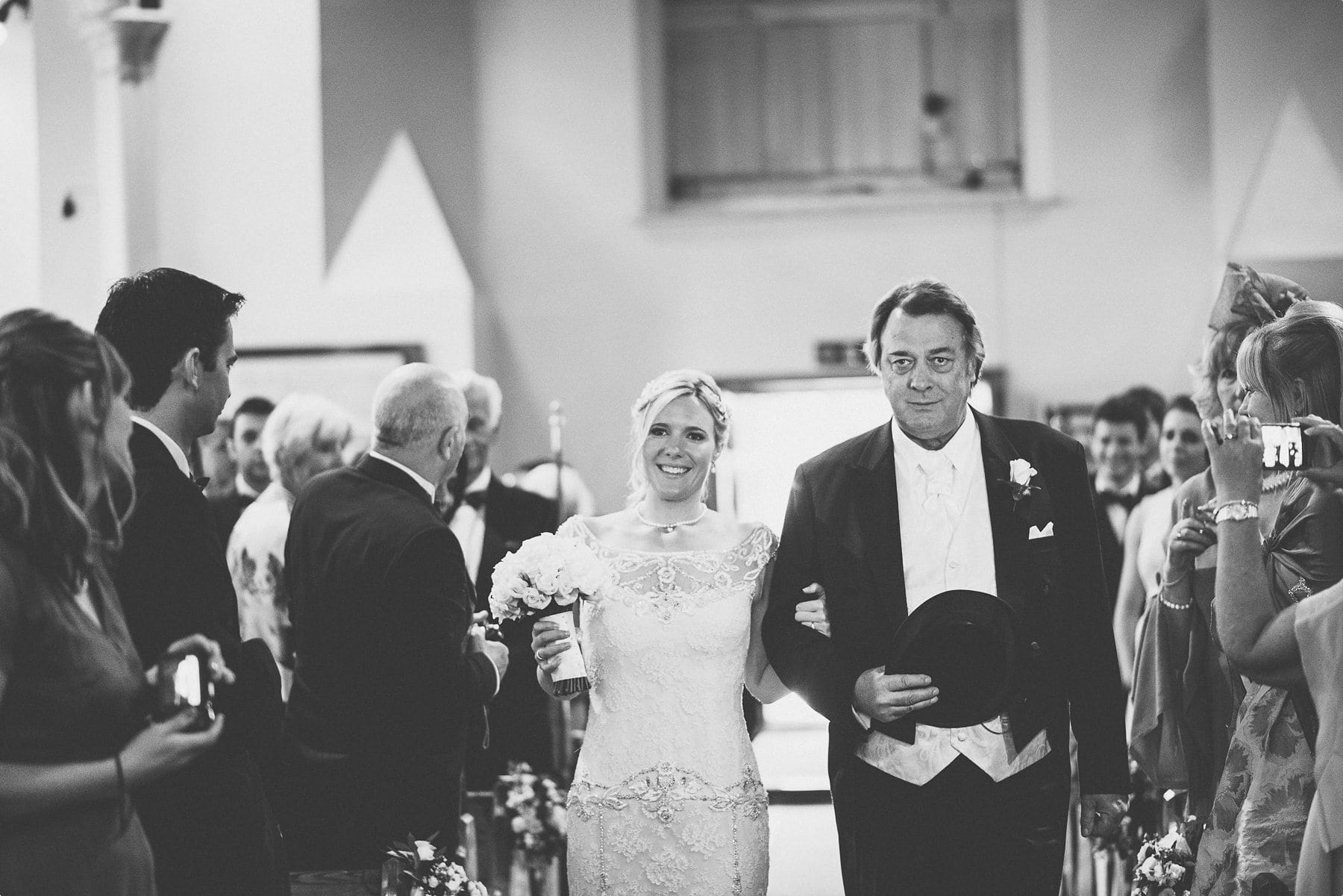 Happy Bride and crying dad walking down St Michael and all Angels church aisle