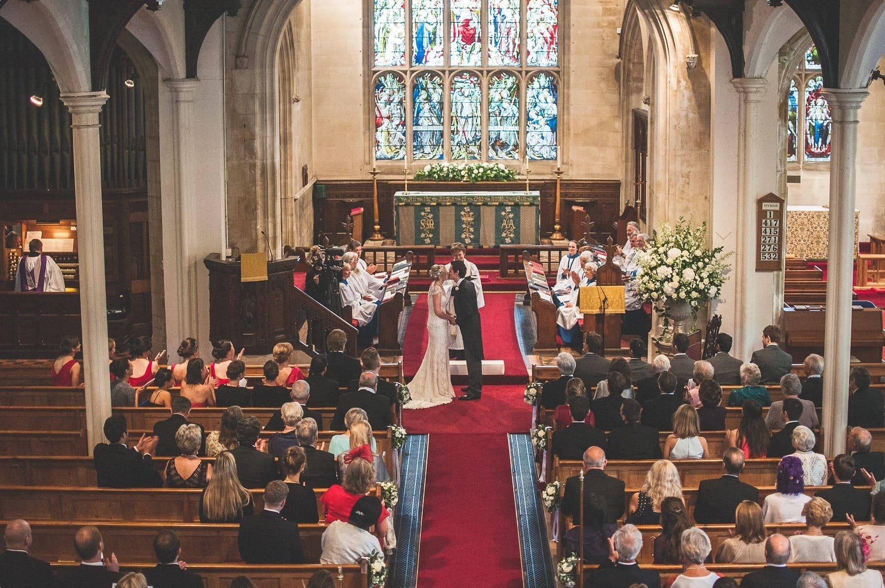 bride and groom kissing at their St Michael and all Angels church wedding ceremony