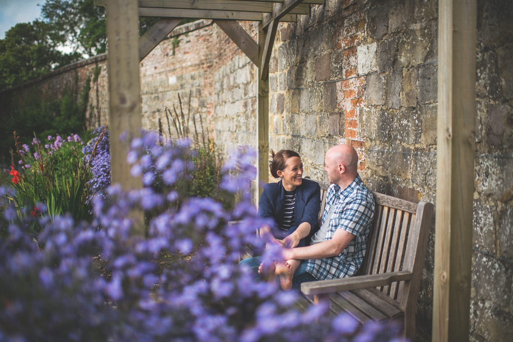 Farnham Castle Misty early morning engagement shoot couple laughing together as they sit on a bench