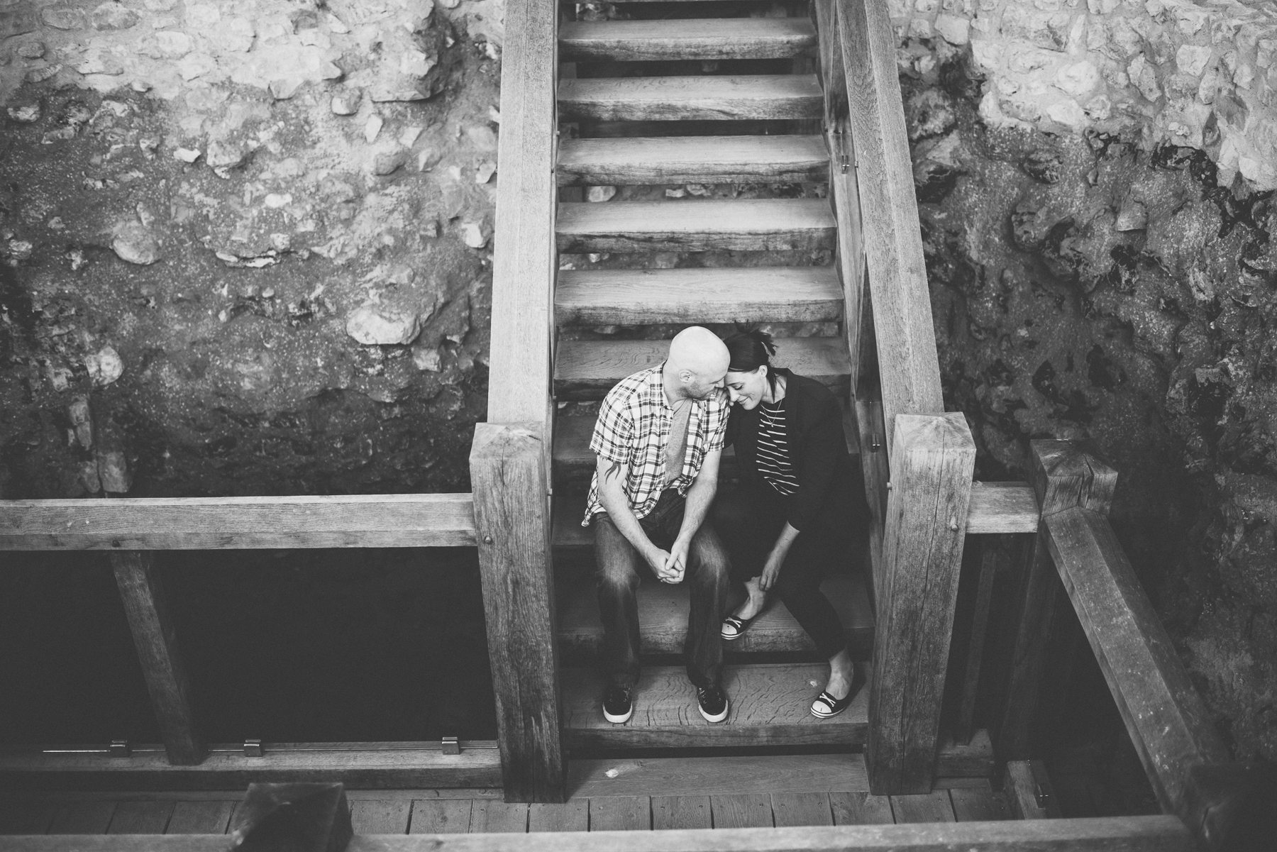 engaged couple sitting on the steps of farnham castle keep well steps on their farnham castle misty early morning engagement shoot by maria assia photography
