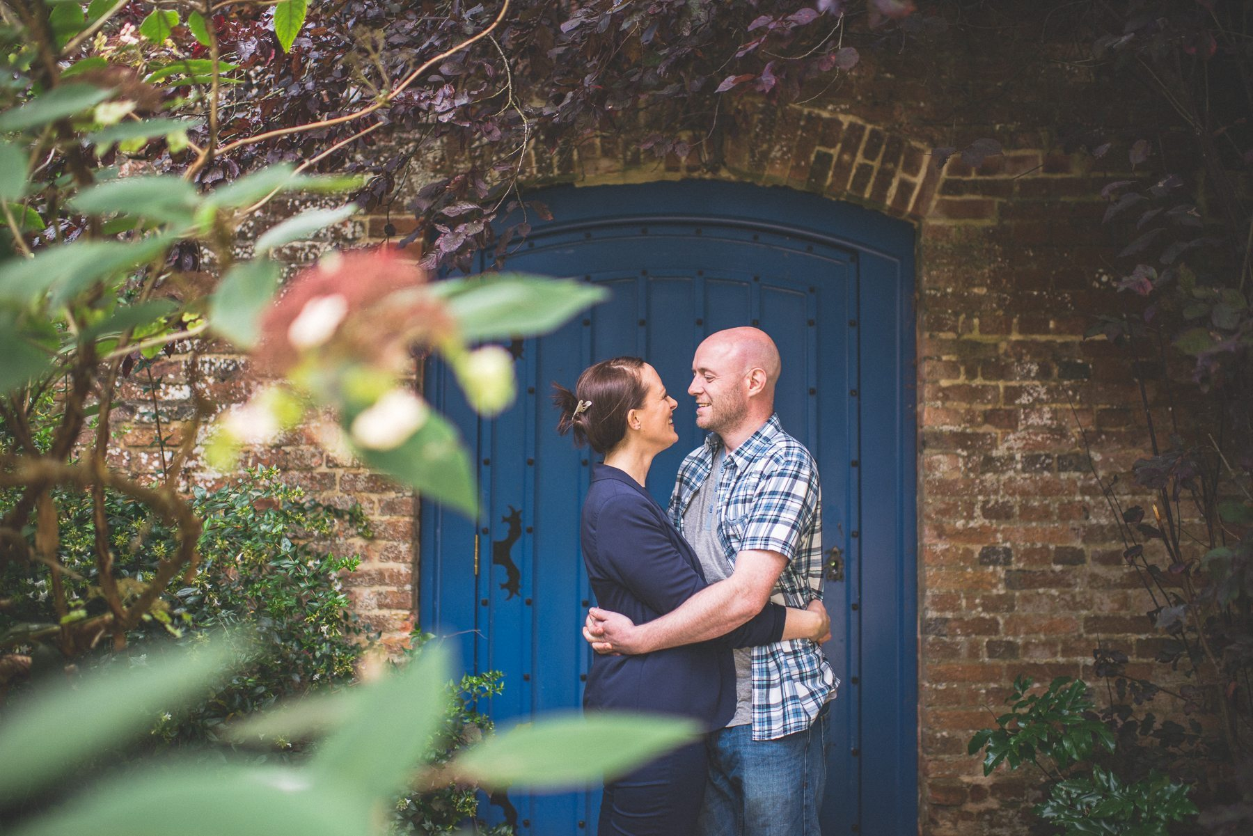 Engagement shoot at Farnham Castle couple laughing as they hug in front of a blue door
