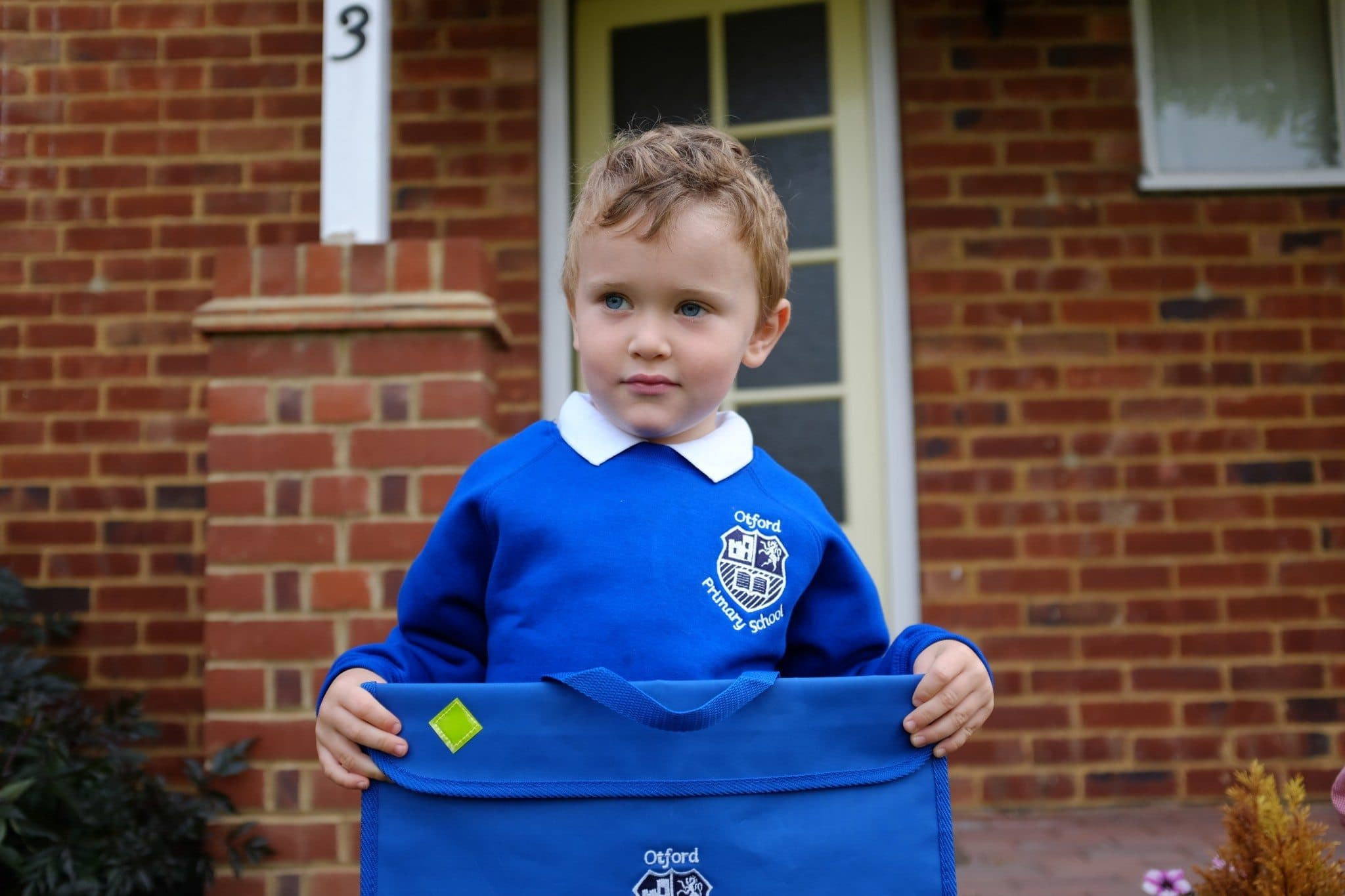 Family ang Children photographer in Sevenoaks Maria Assia's son Little boy in school uniform holding his school book bag on his first day of school