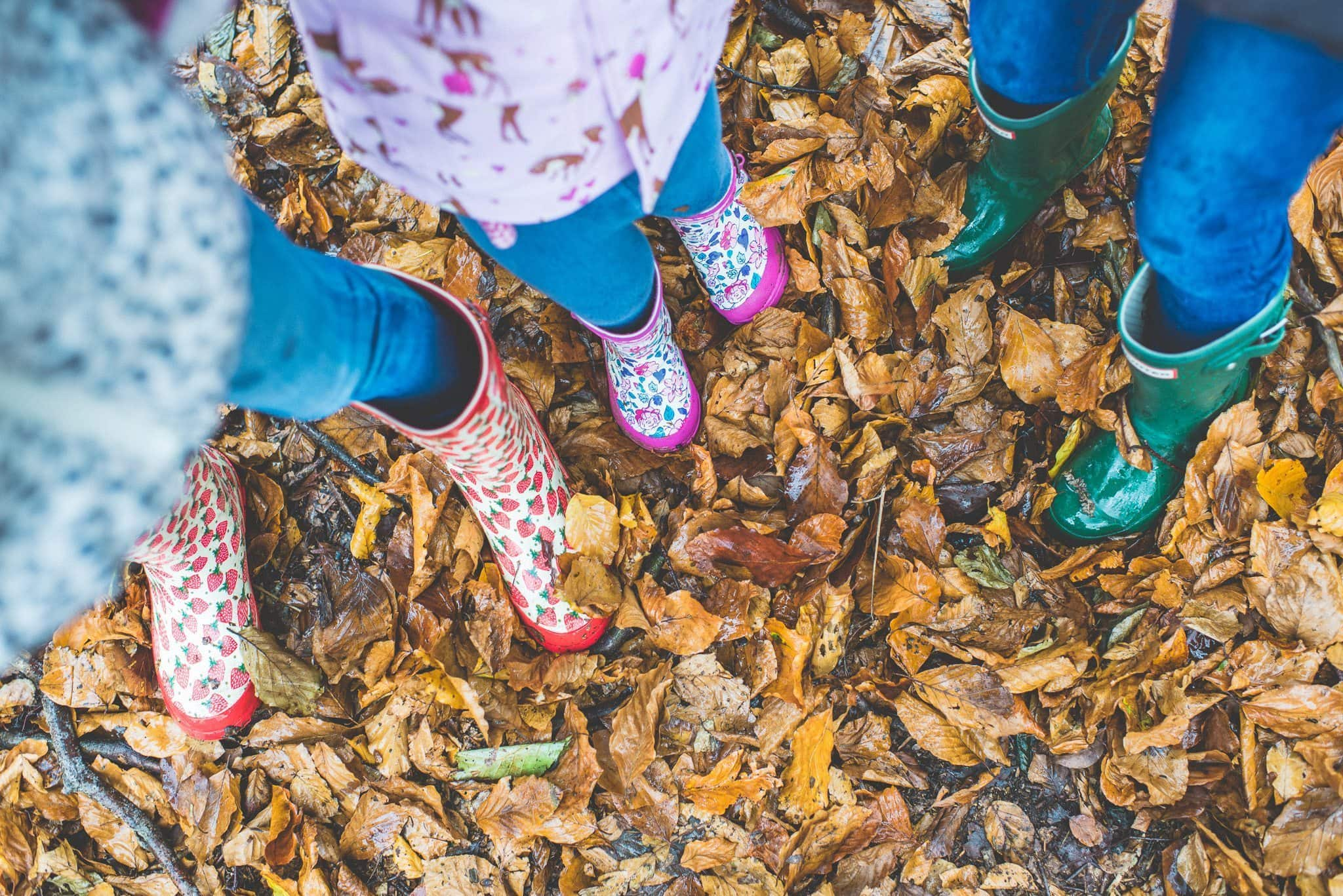 Three sets of children's wellies kicking up autumn leaves at Knole Park in Sevenoaks