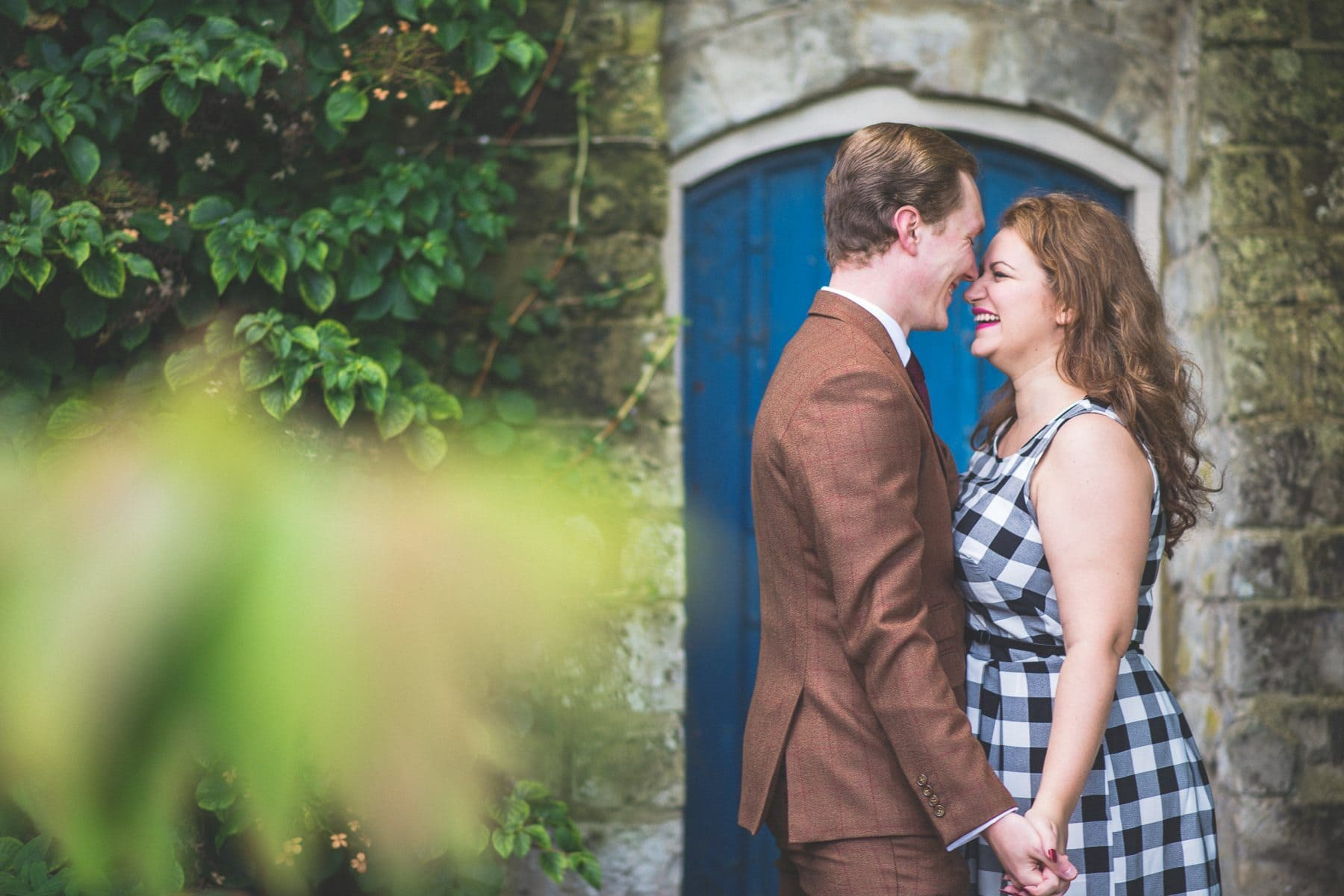 Couple laughing in a blue doorway at Farnham Castle pre-wedding shoot