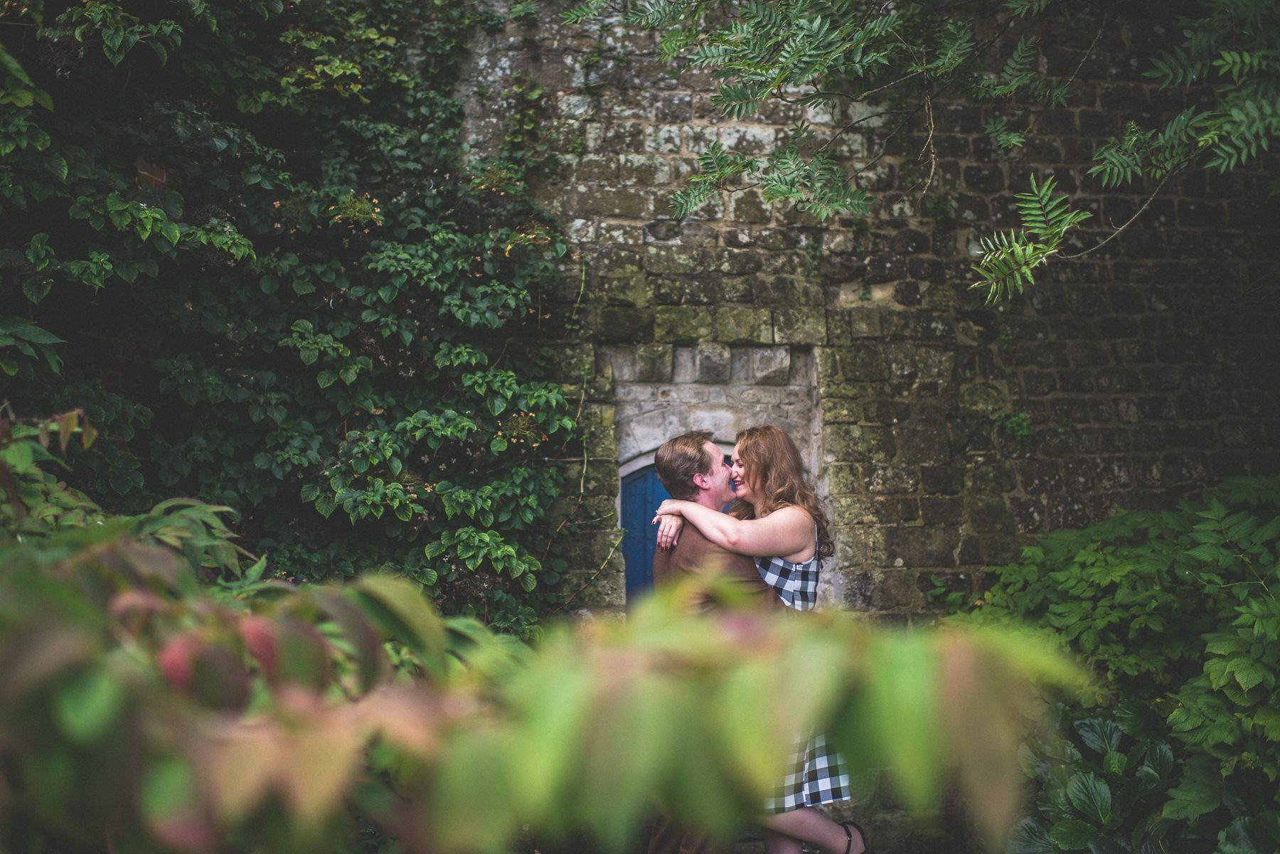 Couple kissing behind blurred leaves at their tweed & petticoats engagement shoot