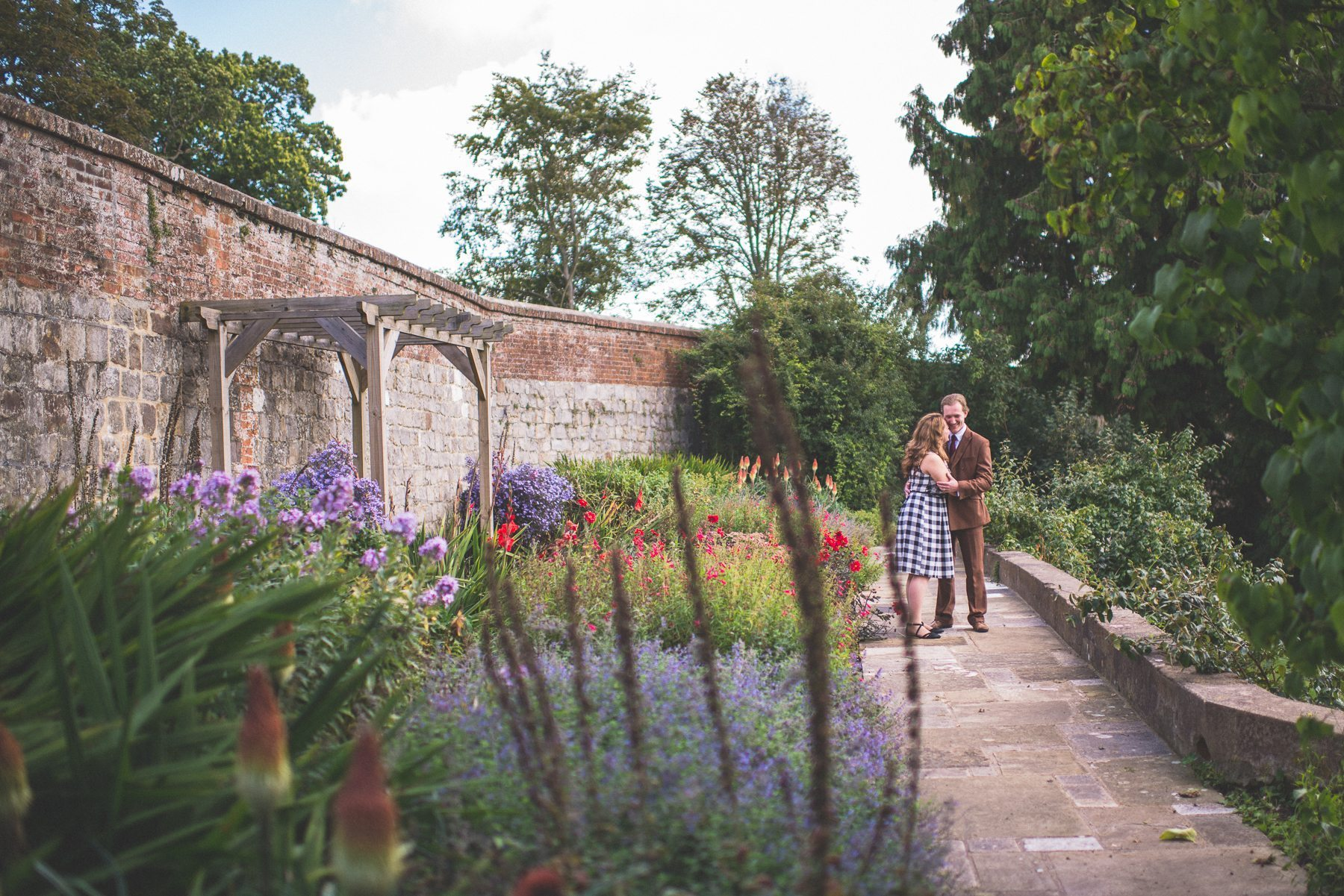 Farnham Castle Tweed & Petticoats pre-wedding shoot couple standing on the wall by Maria Assia Photography