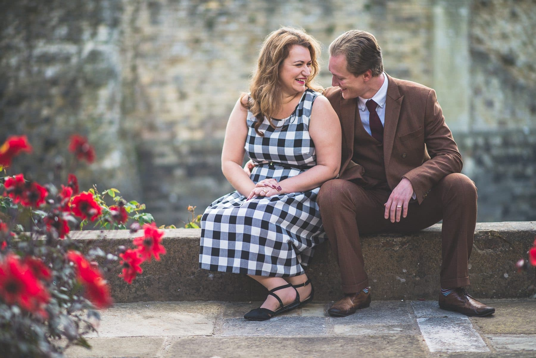 Couple laughing on a wall at Farnham Castle