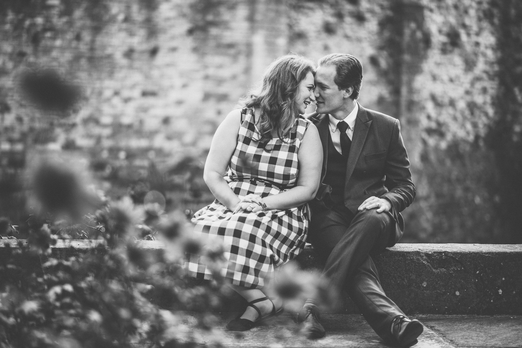 Couple sitting on a wall at Farnham Castle on their tweed & petticoats engagement shoot