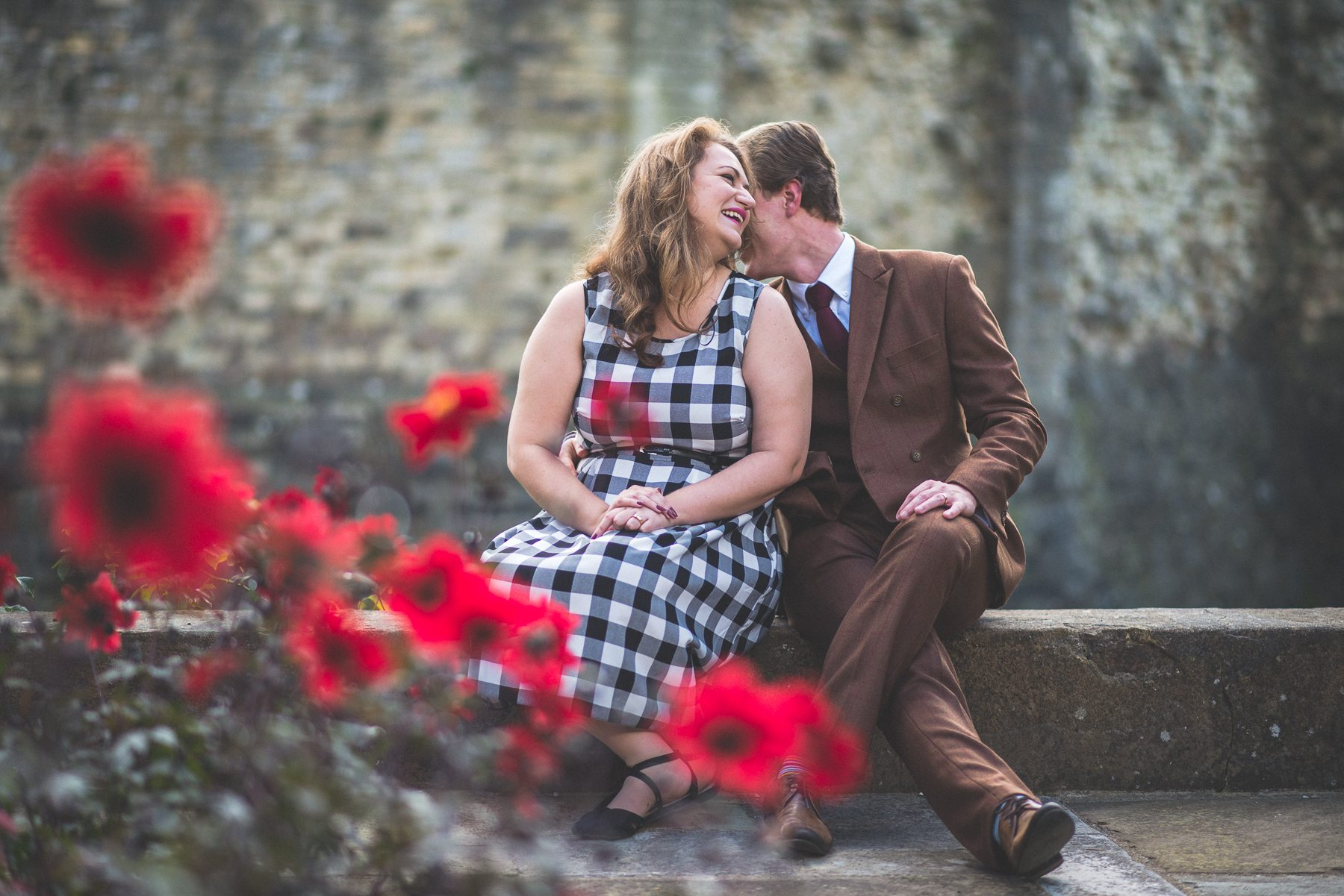 Couple sitting on a wall and the man is kissing the girl's shoulder at Farnham Castle on their tweed & petticoats engagement shoot