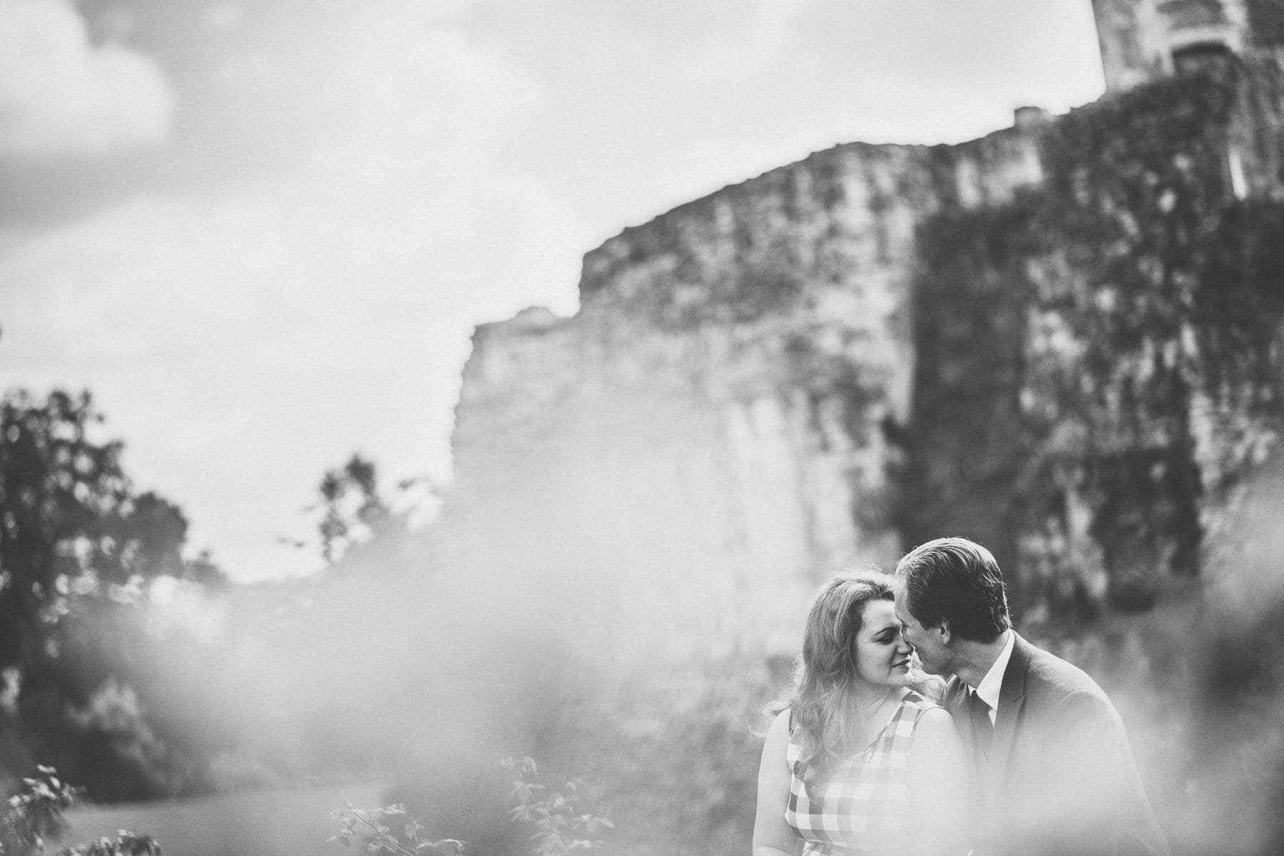 Couple sitting on a wall at Farnham Castle and Farnham Castle Keep nearly kissing in black and white on their Farnham Castle tweed & petticoats pre-wedding shoot by natural alternative creative wedding photographer Maria Assia Photography