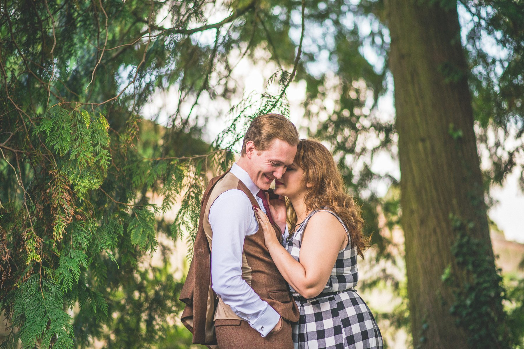 Engaged couple leaning into each other beneath a tree at Farnham Castle