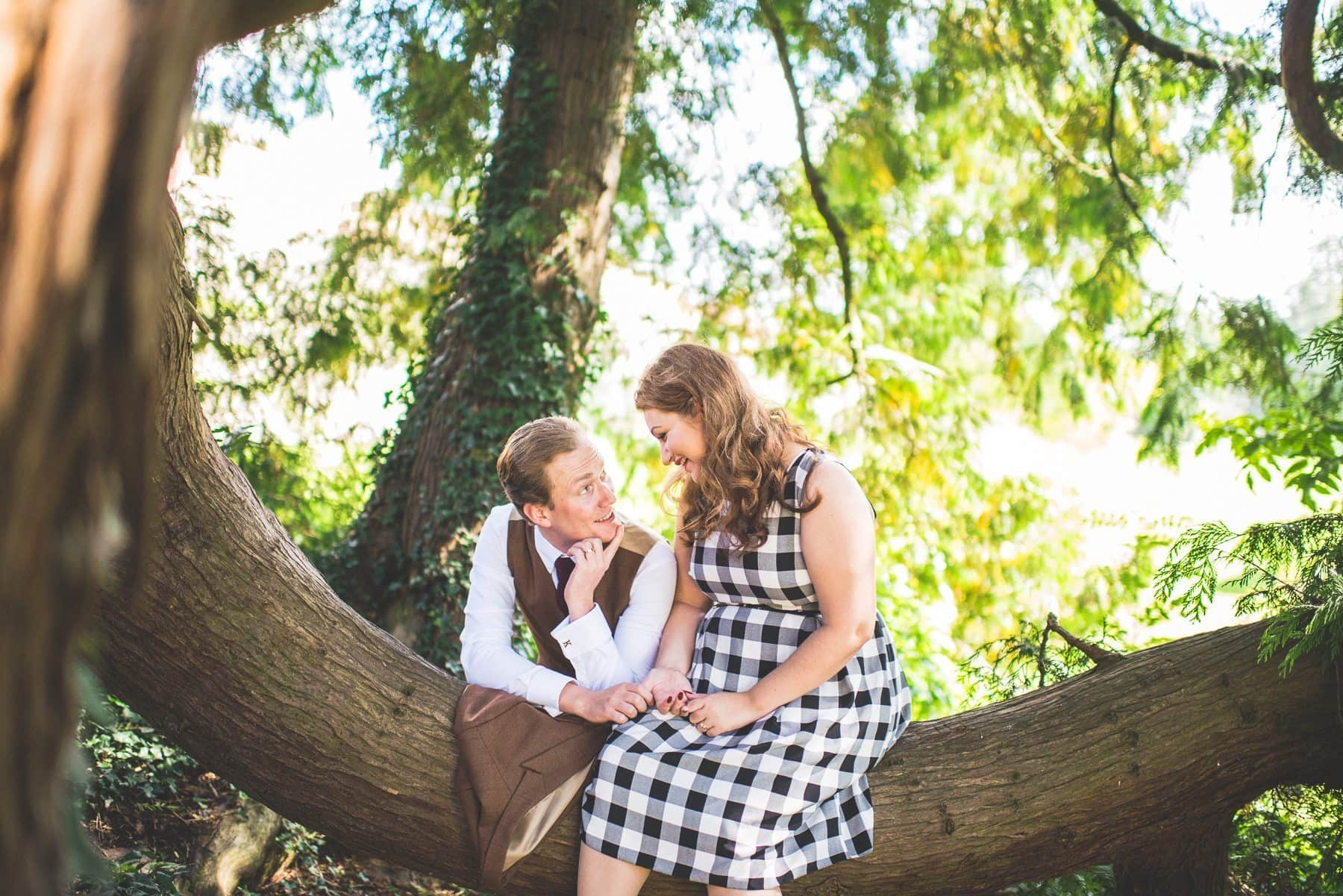 Engaged couple joking around at a Farnham Castle tree on their creative and natural tweed & petticoats engagement shoot