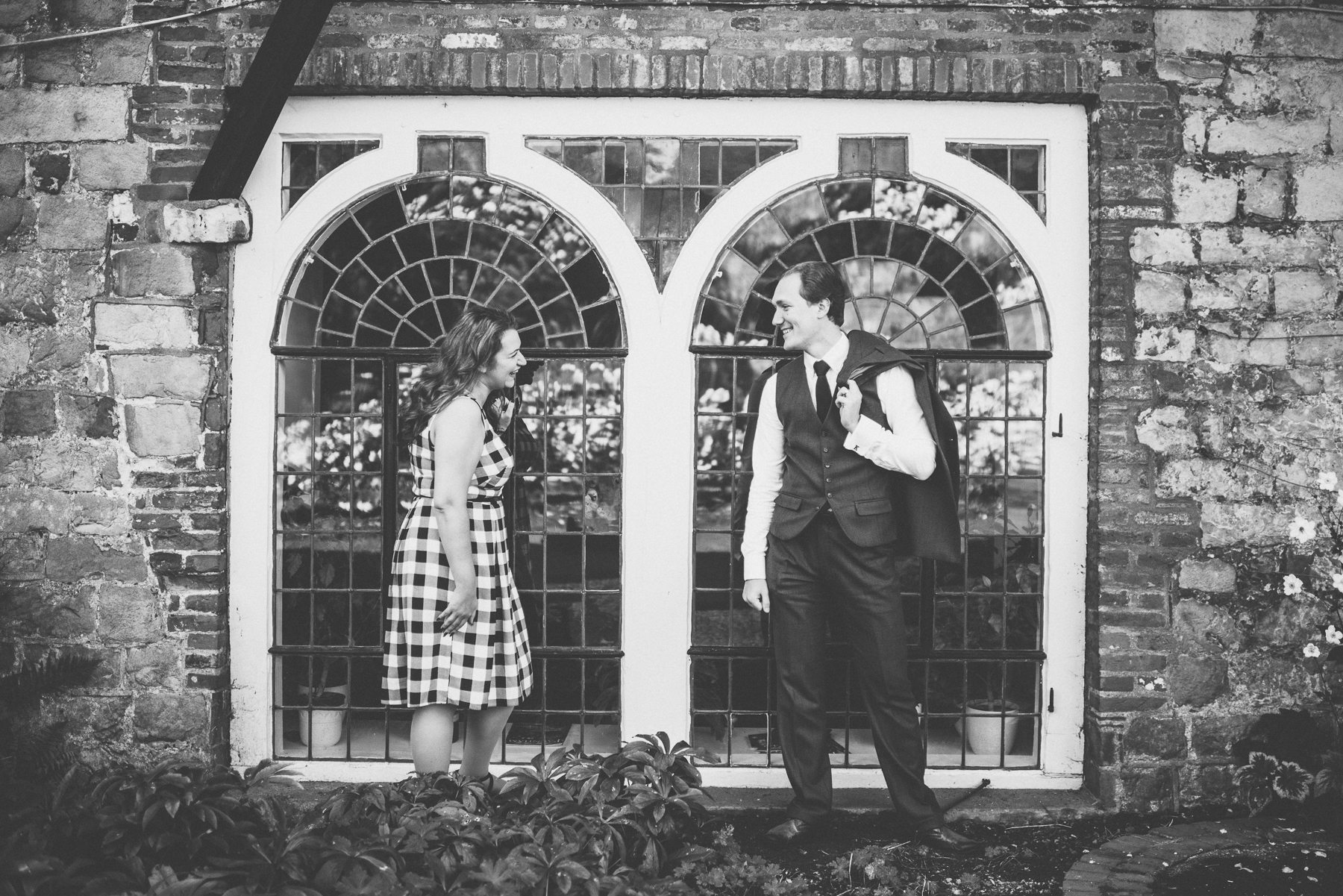 Engaged couple laughing in front of stained glass window of Farnham Castle Bishop's Palace