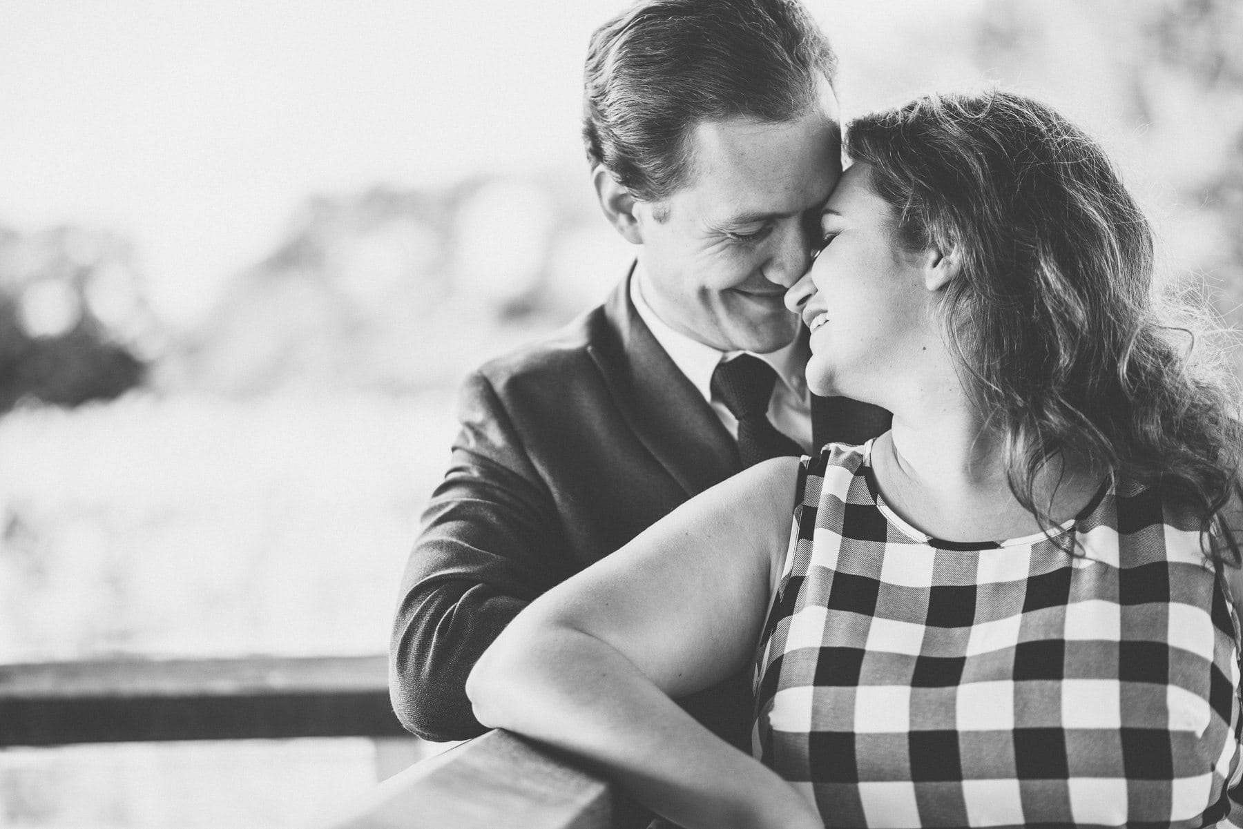 black and white photo of an engaged couple leaning in closely at Farnham Castle Keep Well railing by natural alternative fun wedding photographer Maria Assia Photography