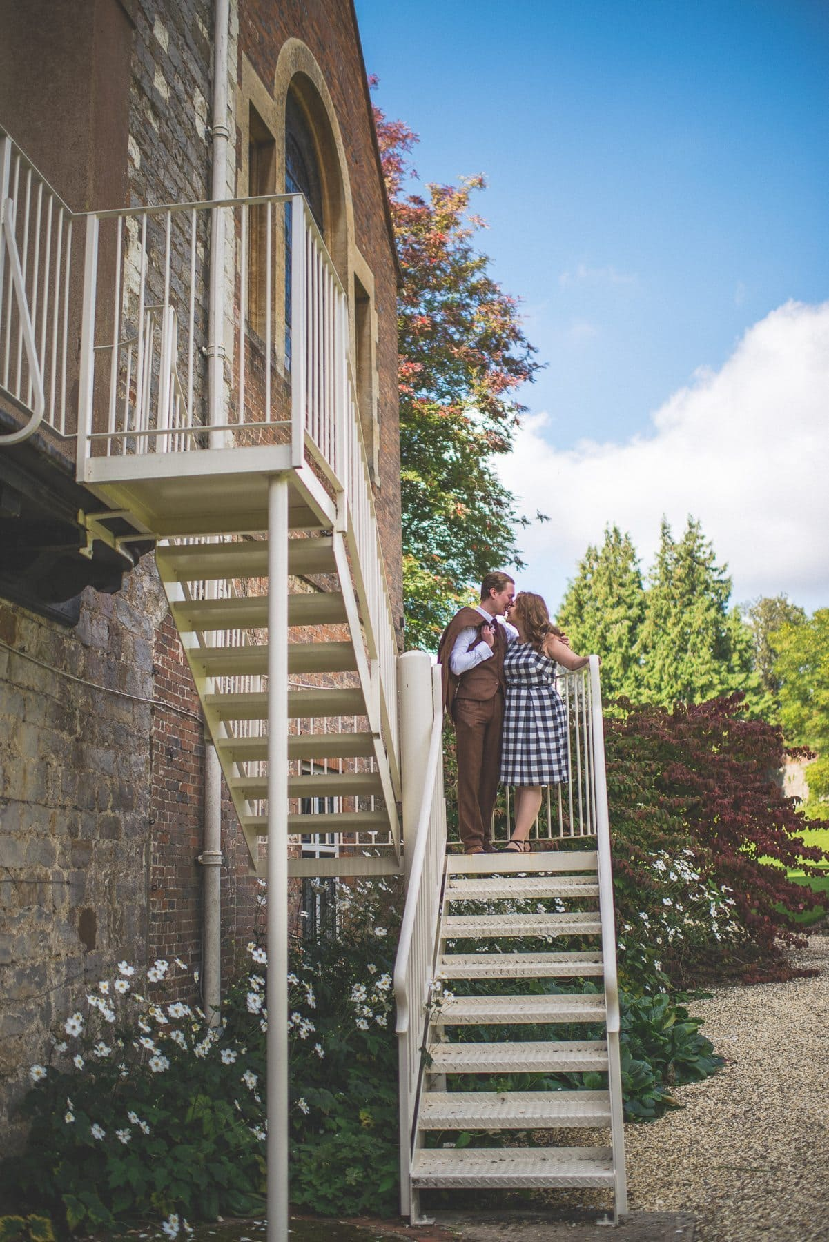 Couple standing and kissing at the stairs of Farnham Castle on their tweed & petticoats pre-wedding shoot captured by alternative wedding photographer maria assia photography
