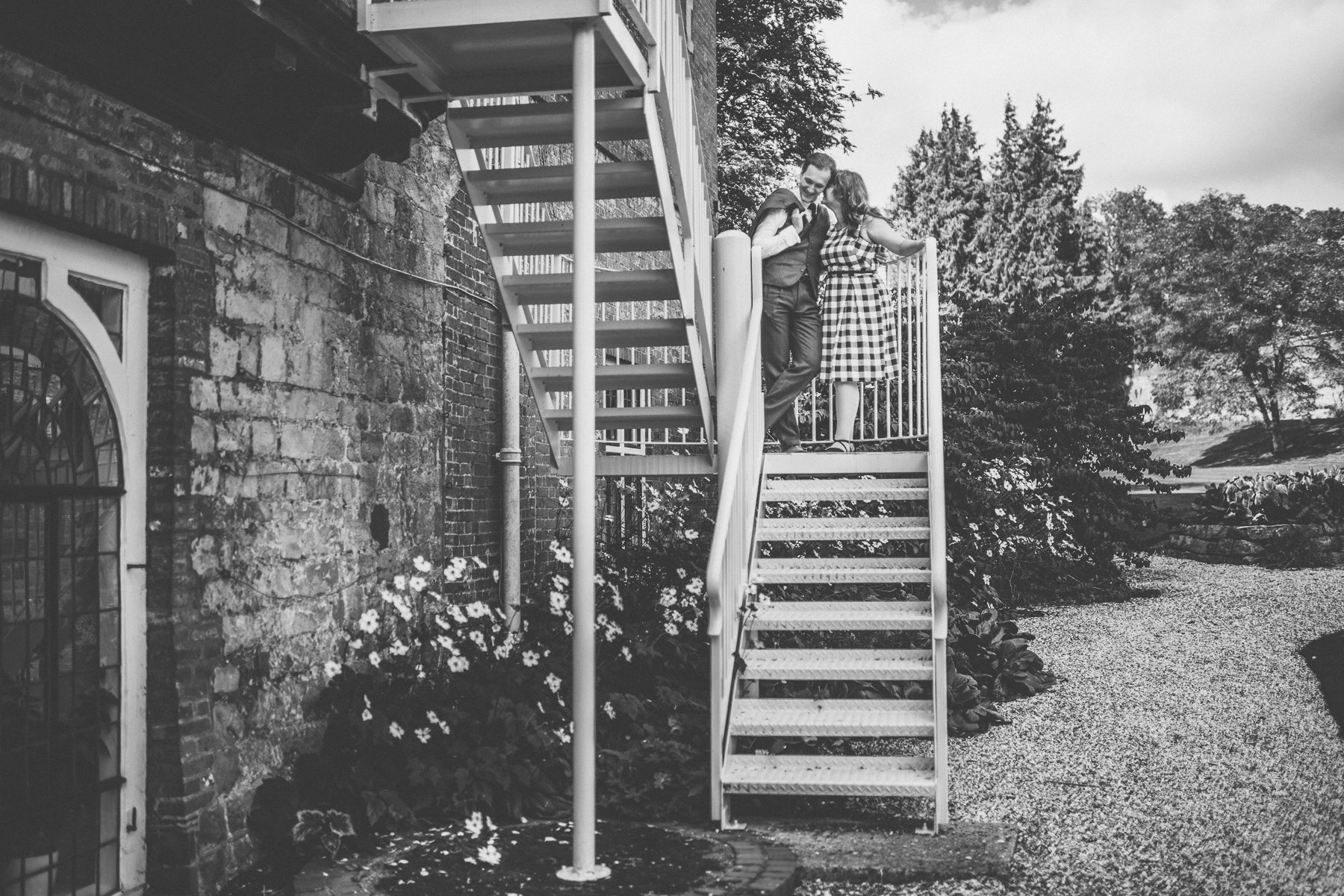 Couple standing and kissing at the stairs of Farnham Castle on their tweed & petticoats pre-wedding shoot captured by alternative wedding photographer maria assia photography in black and white