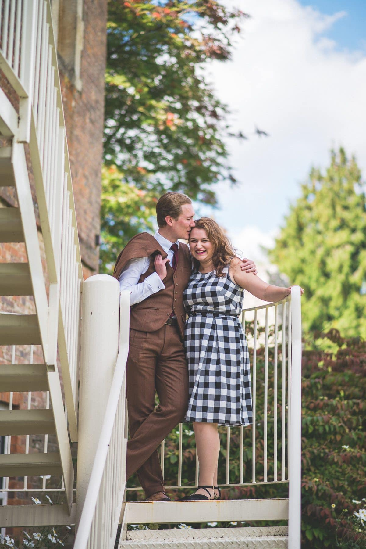 Couple standing and kissing at the stairs of Farnham Castle Bishop Palace on their tweed & petticoats pre-wedding shoot captured by alternative wedding photographer maria assia photography