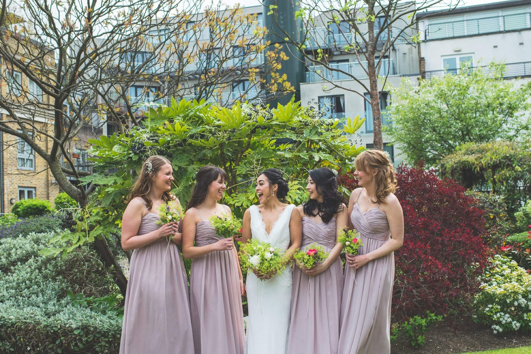 Bride laughing with her bridesmaids