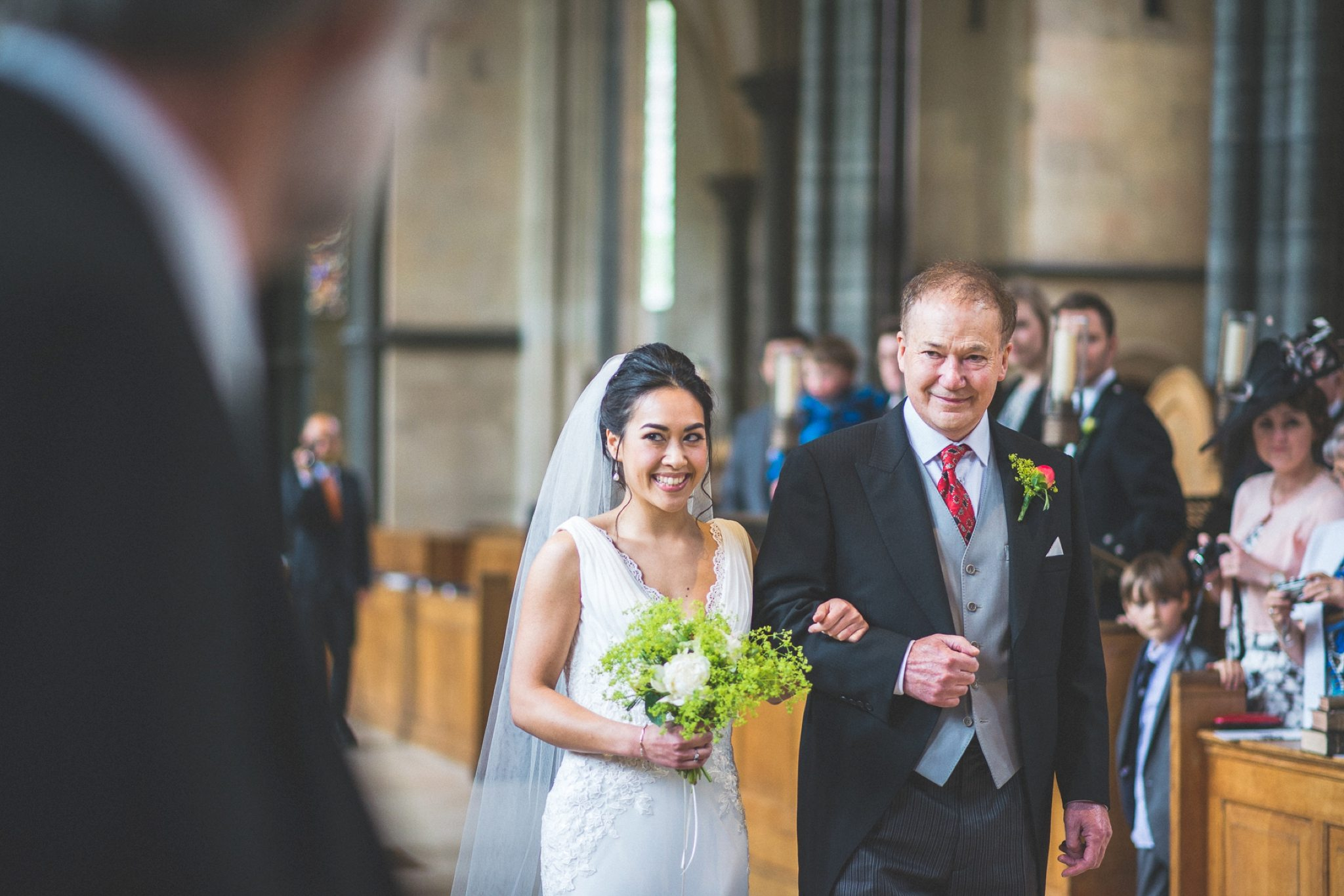 Bride walking down the aisle at Temple church seeing the groom look on his face and smiling