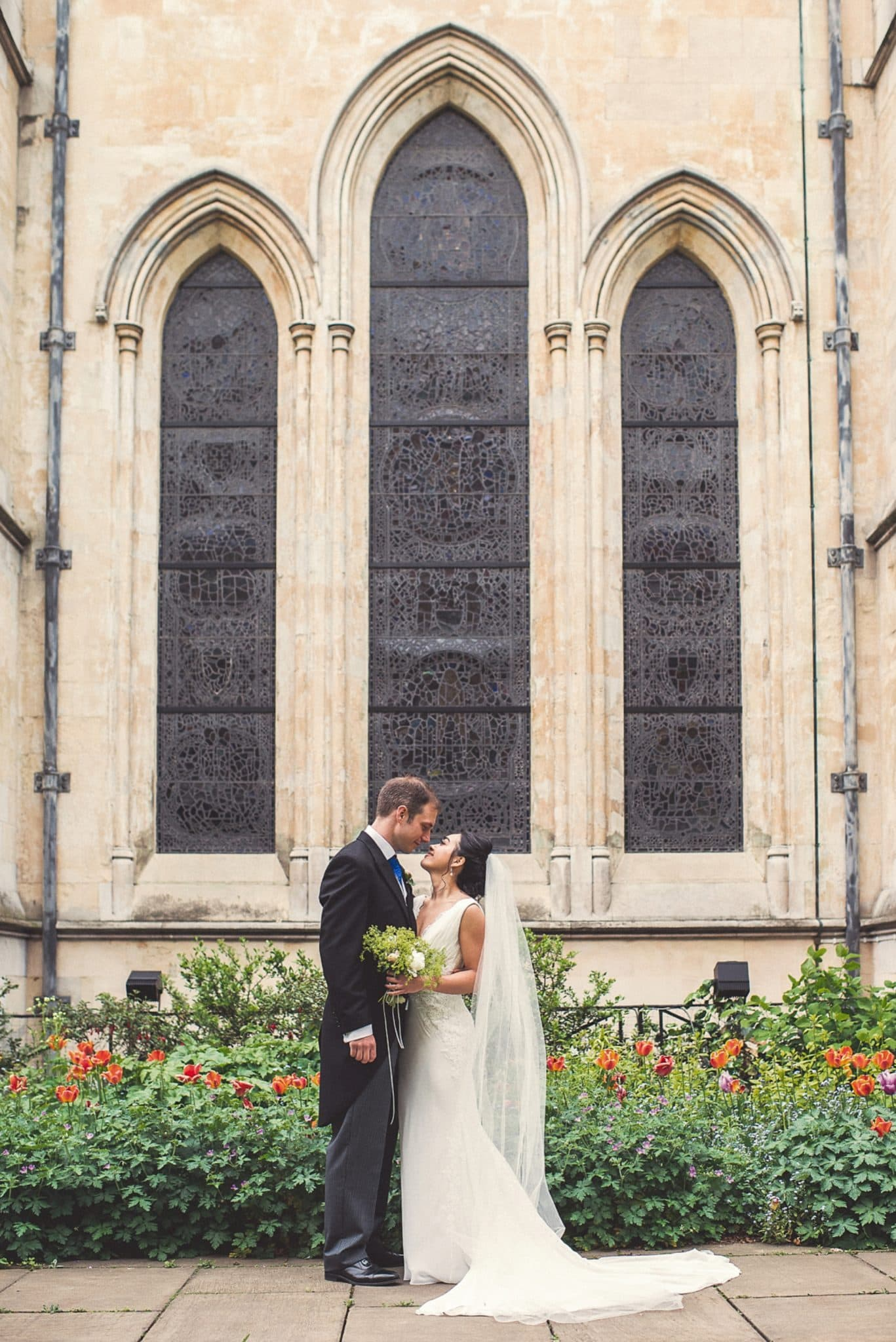 Bride and Groom stand in front of the stained glass windows of Temple Church in London