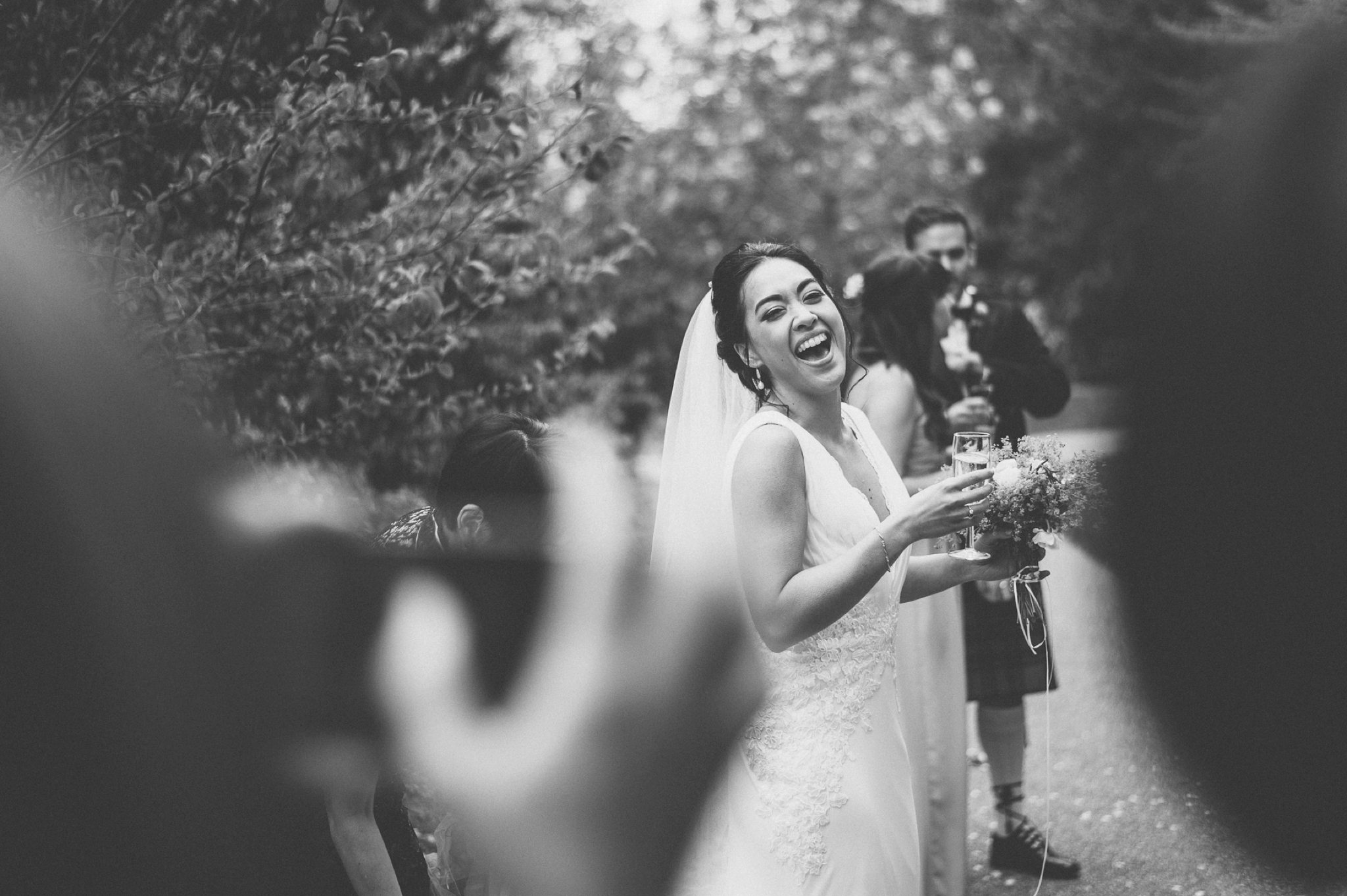 Bride laughing at her guests as they take photos of her at her Two Temple Place Wedding
