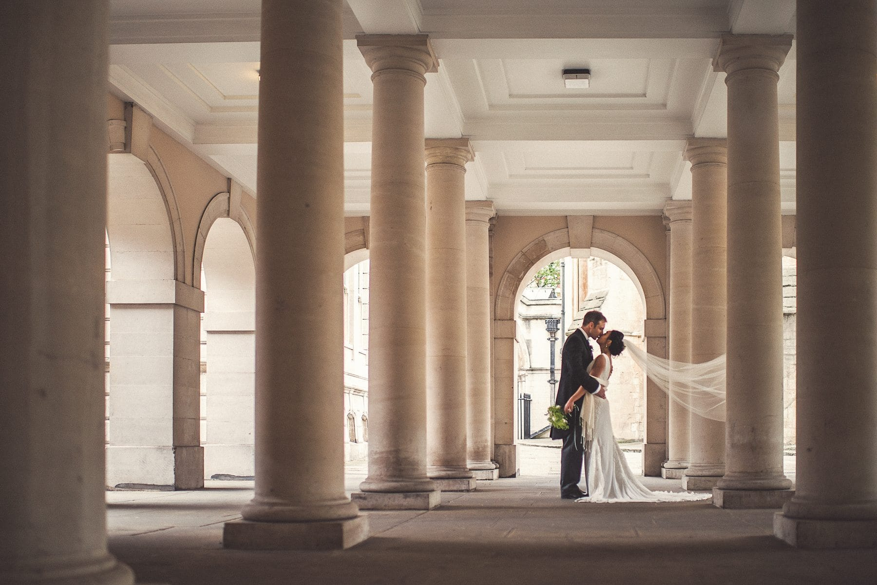 Bride and Groom kiss among the pillars at Temple Church